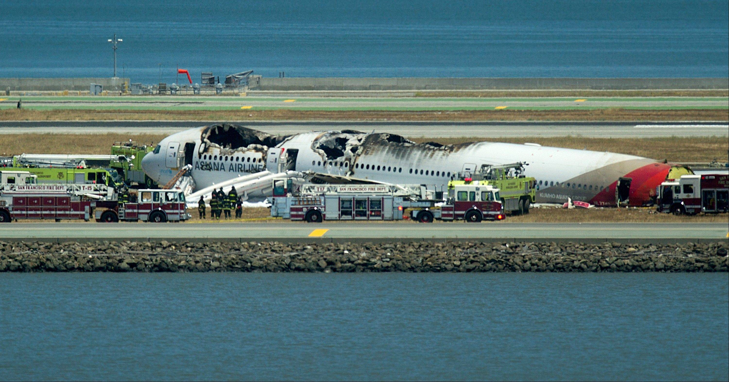 A fire truck sprays water on Asiana Flight 214 after it crashed at San Francisco International Airport on Saturday, July 6, 2013, in San Francisco.