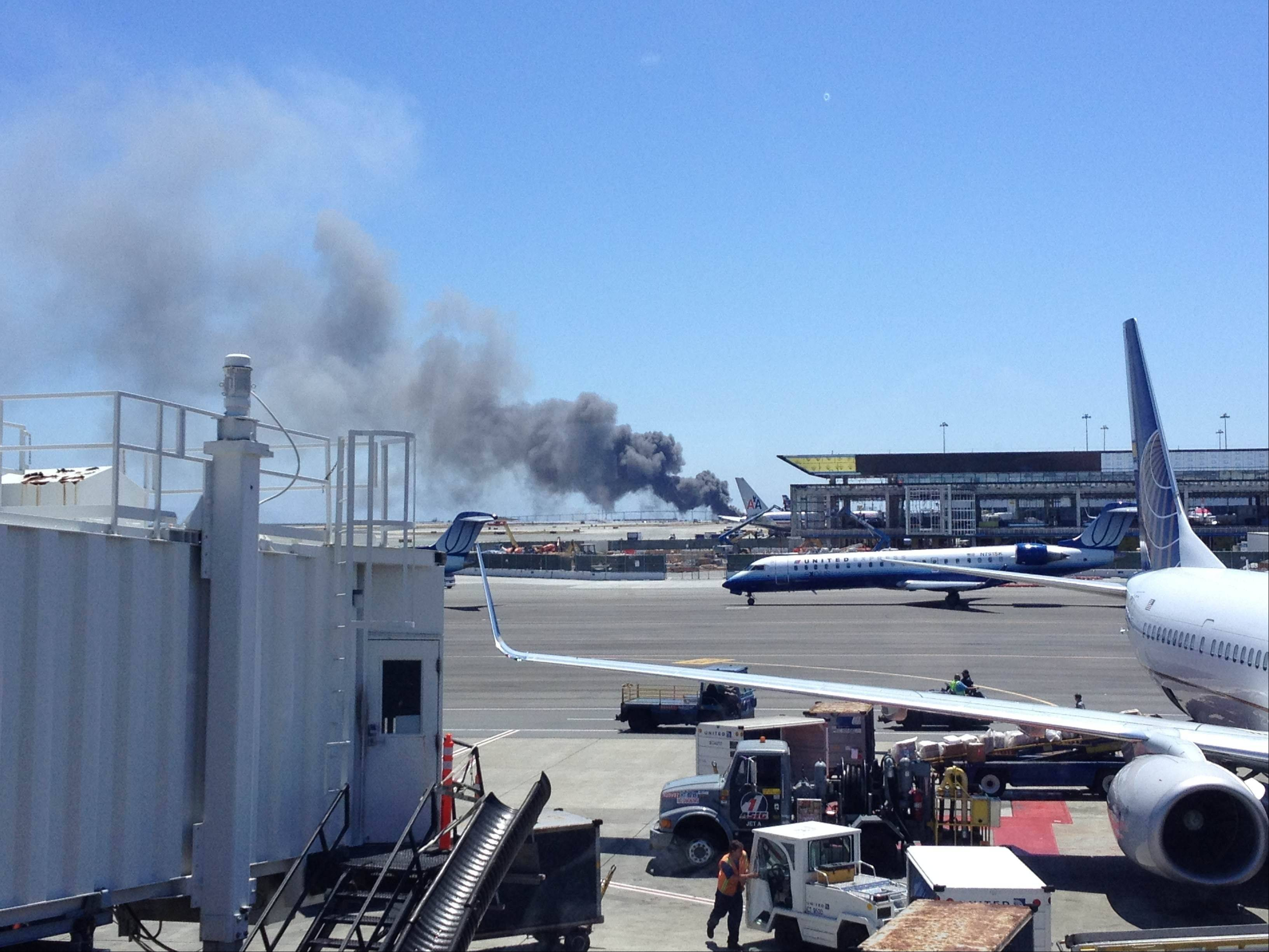This photo provided by Zach Custer shows smoke rising from what a federal aviation official says was an Asiana Airlines flight crashing while landing at San Francisco airport on Saturday, July 6, 2013. It was not immediately known whether there were any injuries.