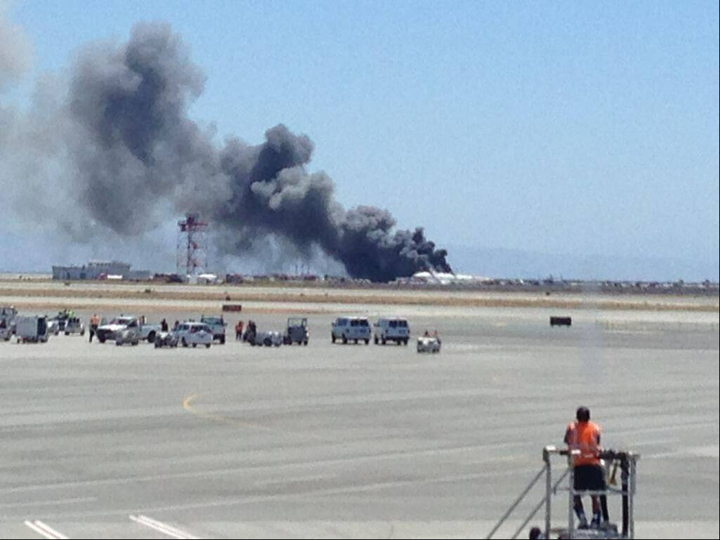 This photo provided by Krista Seiden shows smoke rising from what a federal aviation official says was an Asiana Airlines flight crashing while landing at San Francisco airport on Saturday, July 6, 2013. It was not immediately known whether there were any injuries.
