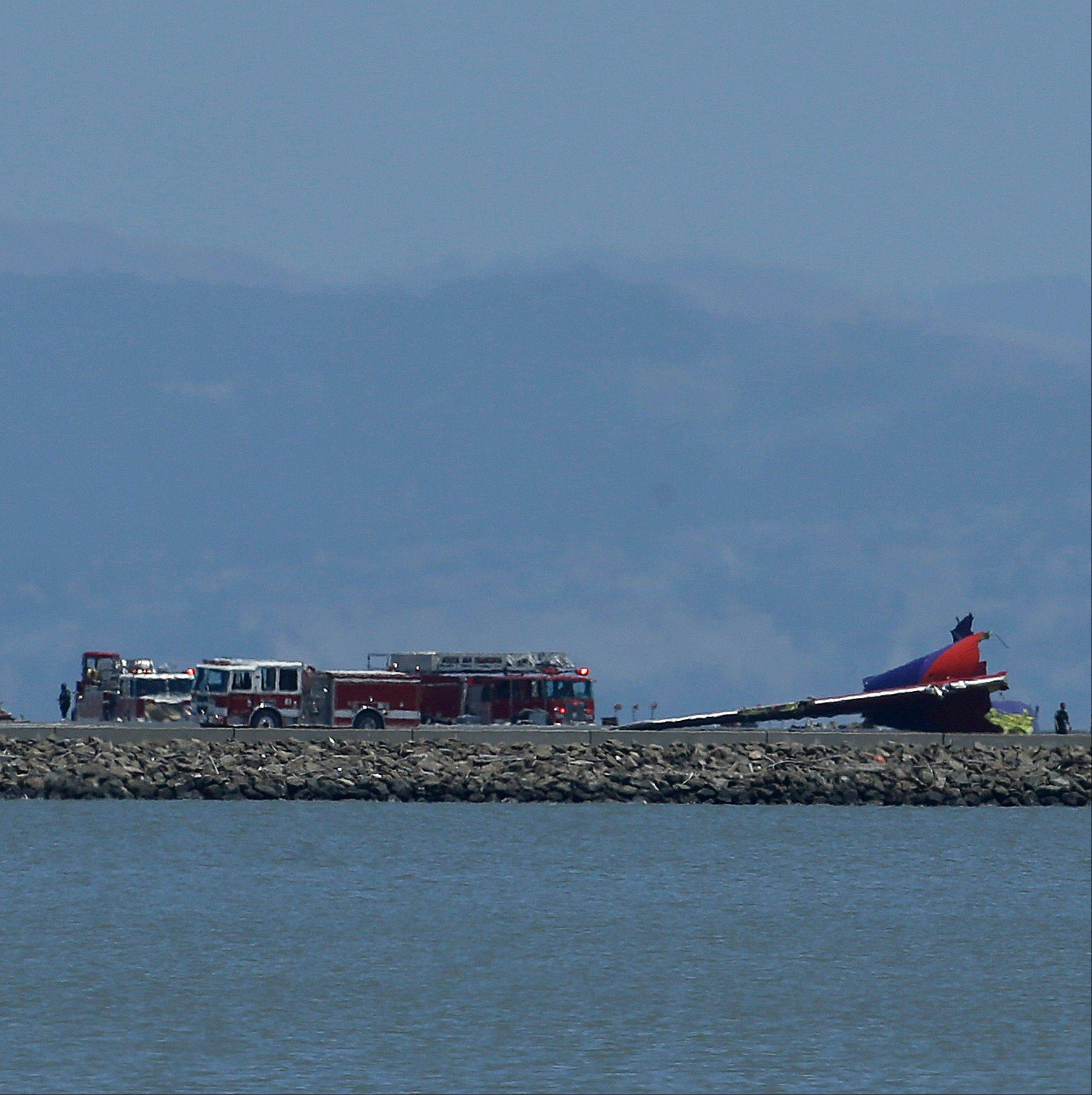 The tail of Asiana Flight 214 is seen, right, after it crashed at San Francisco International Airport in San Francisco, Saturday, July 6, 2013.