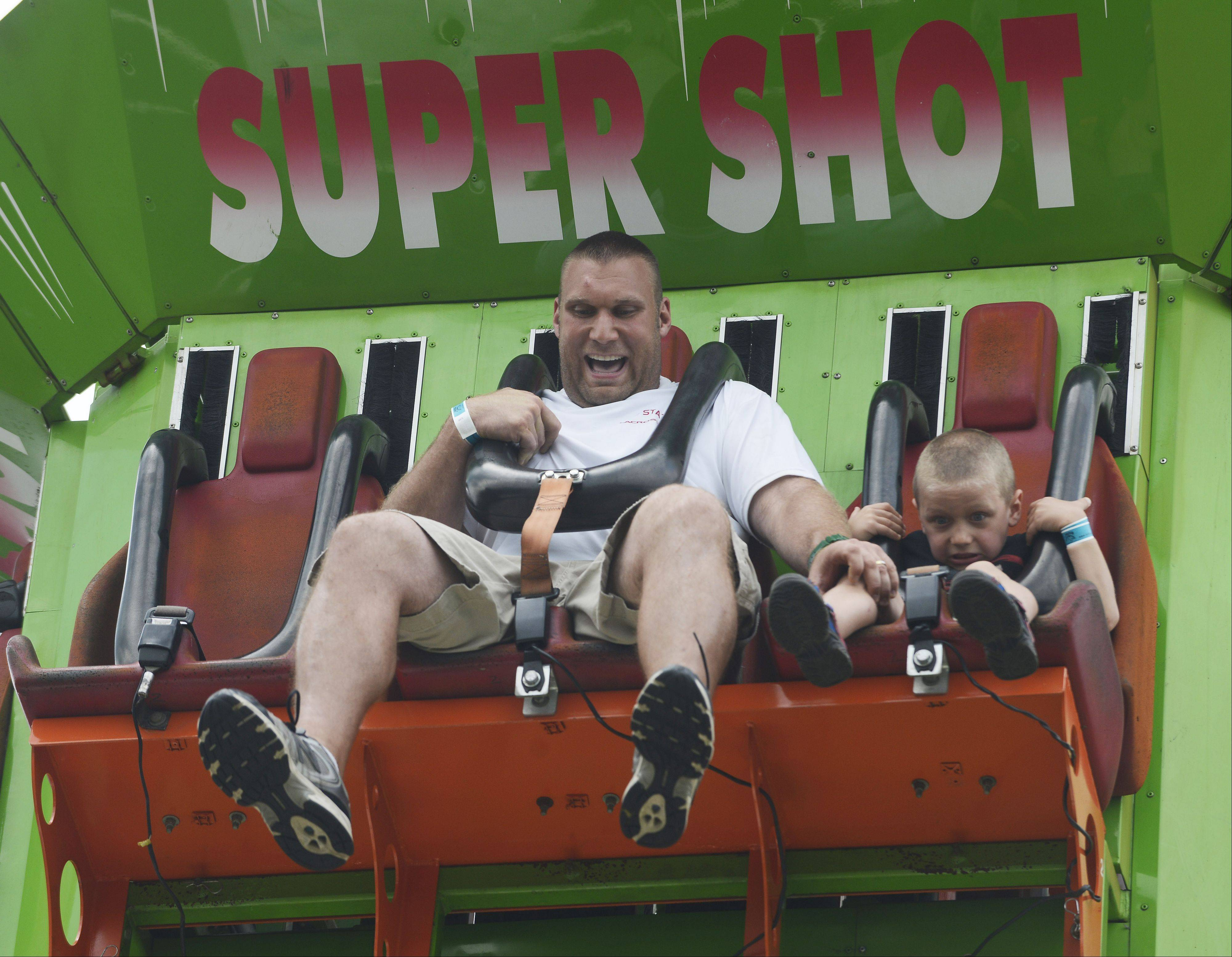 "Justin Georgacakis of Mount Prospect and his 5-year old son, Cheydon, react to the feeling of free-fall on the ""Super Shot"" during the Mount Prospect Lions Club Festival at Melas Park Saturday."