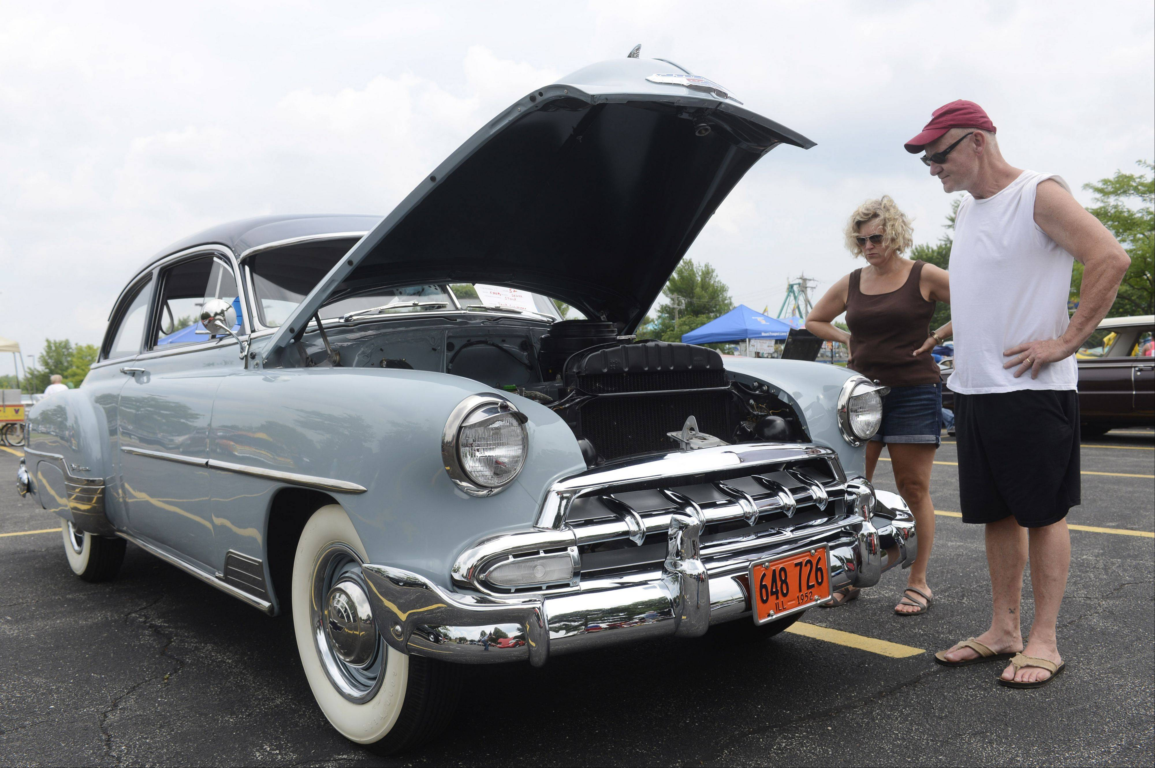 Susan and Bill Treece of Arlington Heights view a 1952 Chevy Deluxe displayed by car owner Jack Shippman during the Mount Prospect Lions Club Festival at Melas Park Saturday.