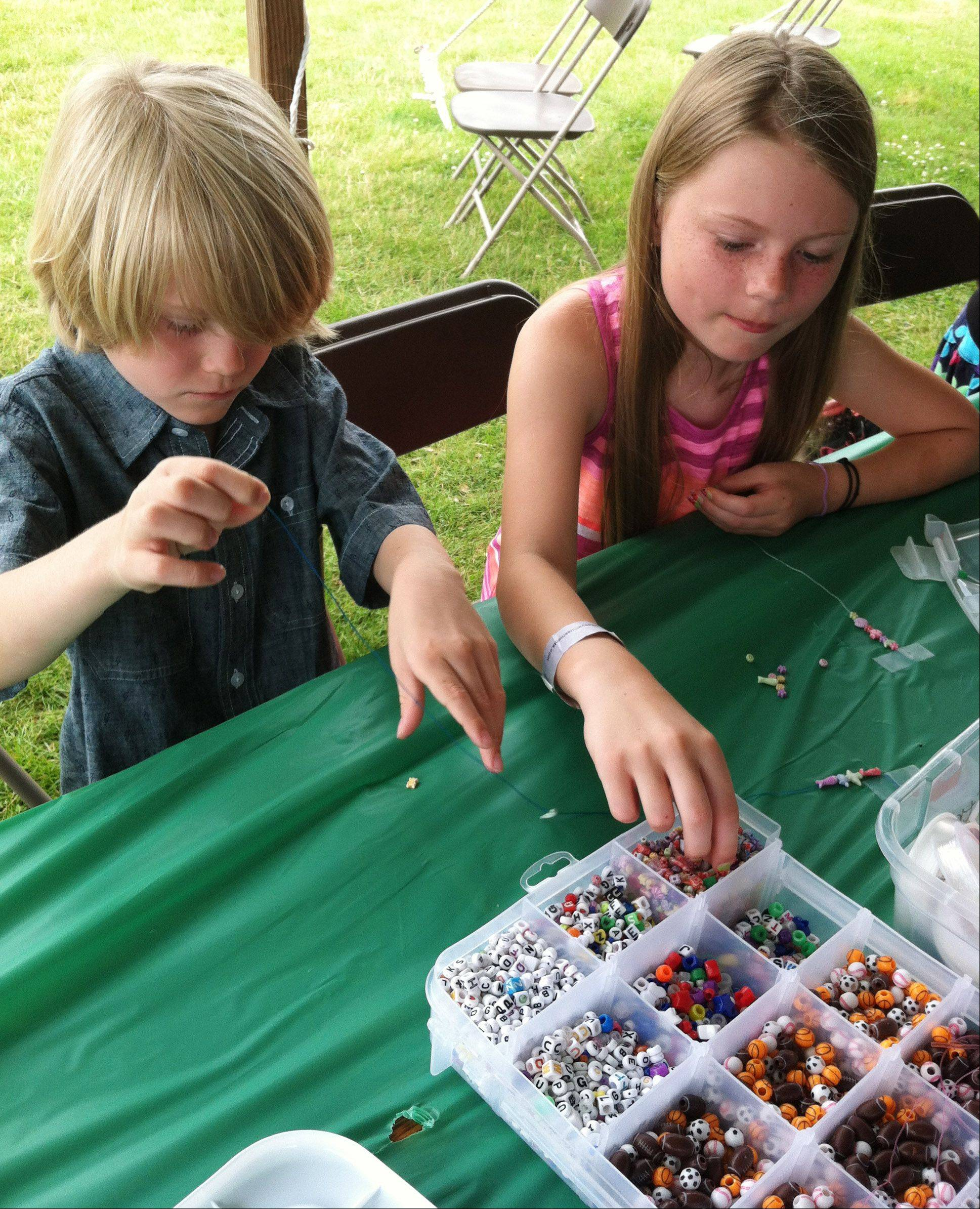 Kira Isbell, 11, and her brother Reid, 7, of Mount Prospect, make bread necklaces Saturday in the childrens tent at Mount Prospect Lions Club Festival. Kids could take advantage of free crafts, face painting, a limbo contest and live-band karaoke.