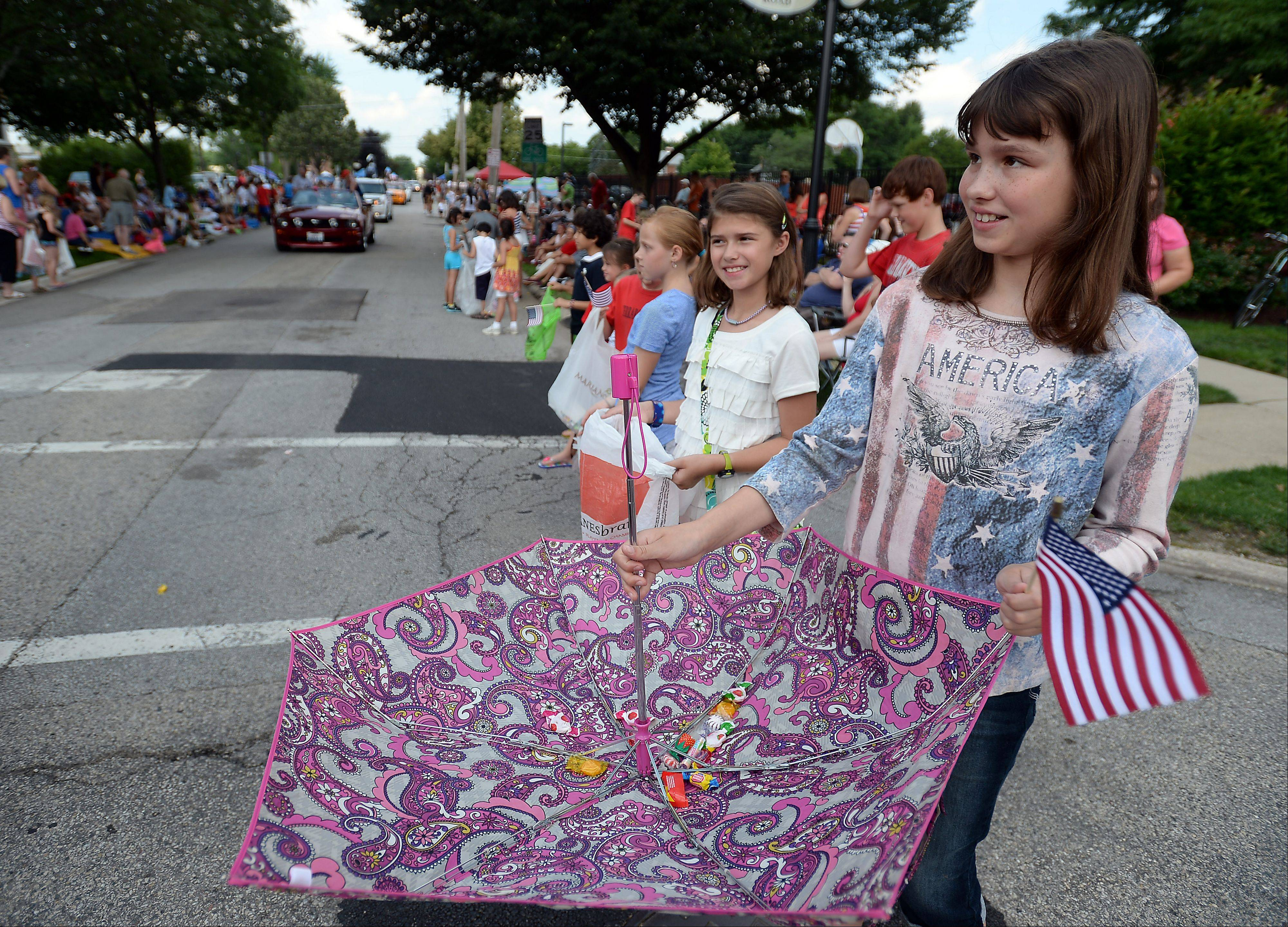 Madisen Blakeslee, 12, makes clever use of an umbrella to catch candy during the Palatine Fourth of July parade on Saturday.