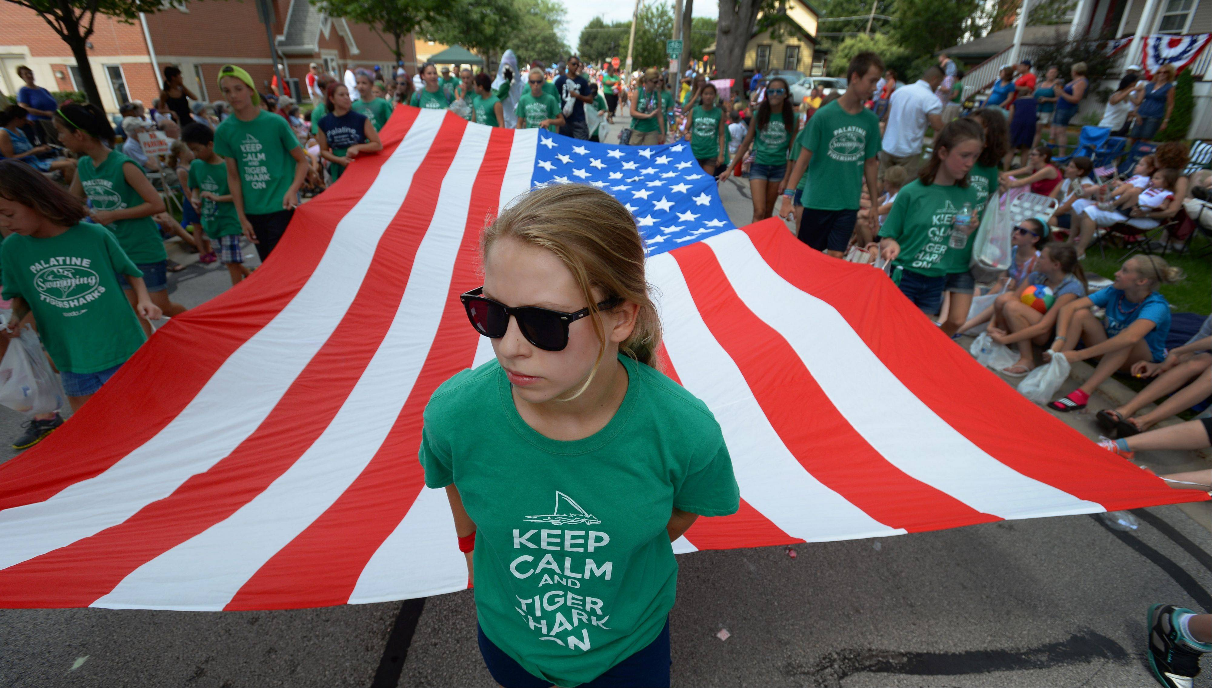 Michaela Kueker, 12, of Palatine leads the charge with the flag during the Palatine Fourth of July parade on Saturday.