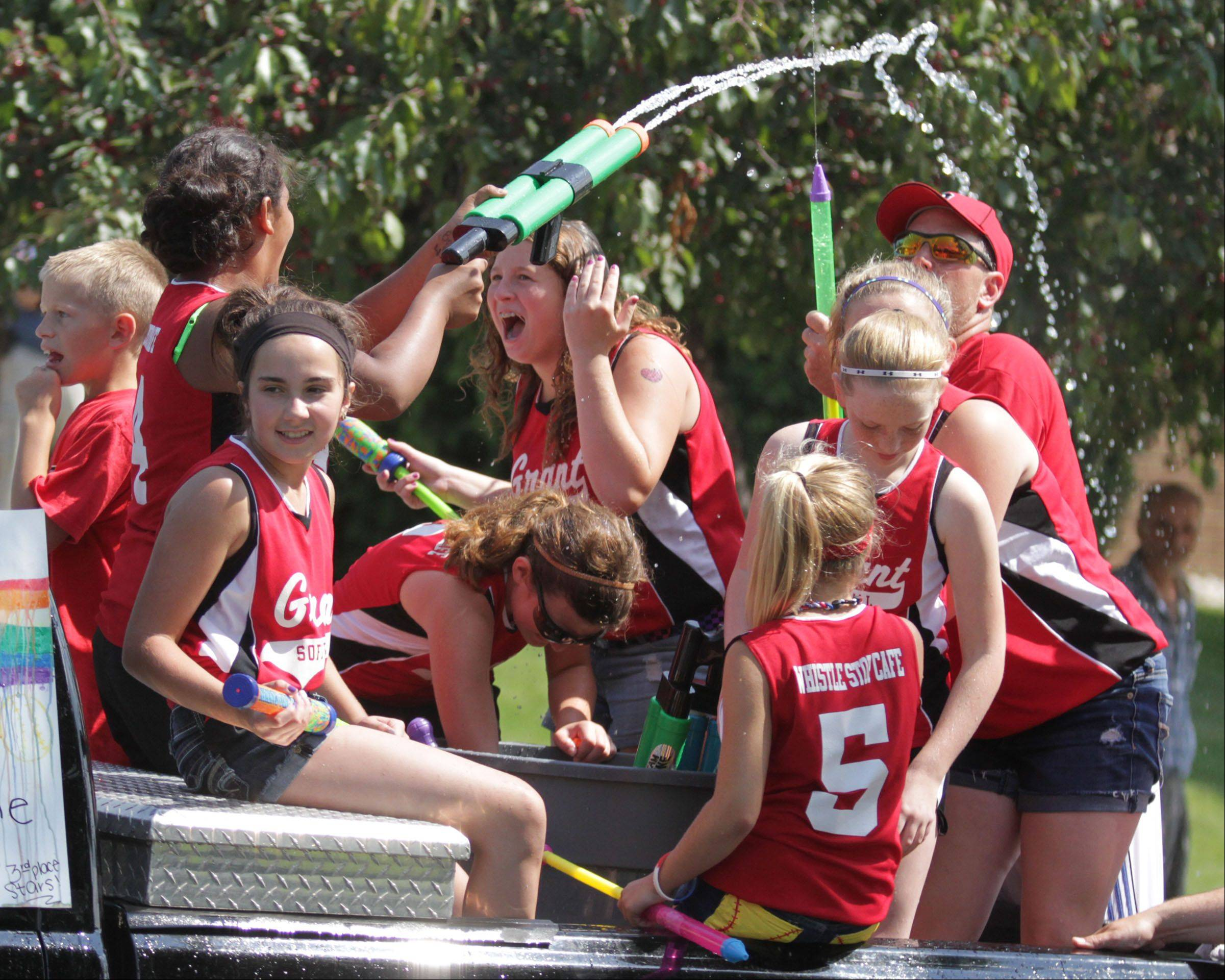 Grant High School summer softball players spray themselves and the crowd watching Saturday's Celebrate Fox Lake parade on Grand Avenue.