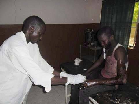 In this photo taken with a mobile phone a doctor attends to a student from Government Secondary School in Mamudo, at the Potiskum General Hospital, Nigeria, after an attack by gunmen on Saturday July 6. Islamic militants attacked a boarding school before dawn Saturday, dousing a dormitory in fuel and lighting it ablaze as students slept, survivors said. At least 30 people were killed in the deadliest attack yet on schools in Nigeria's embattled northeast.