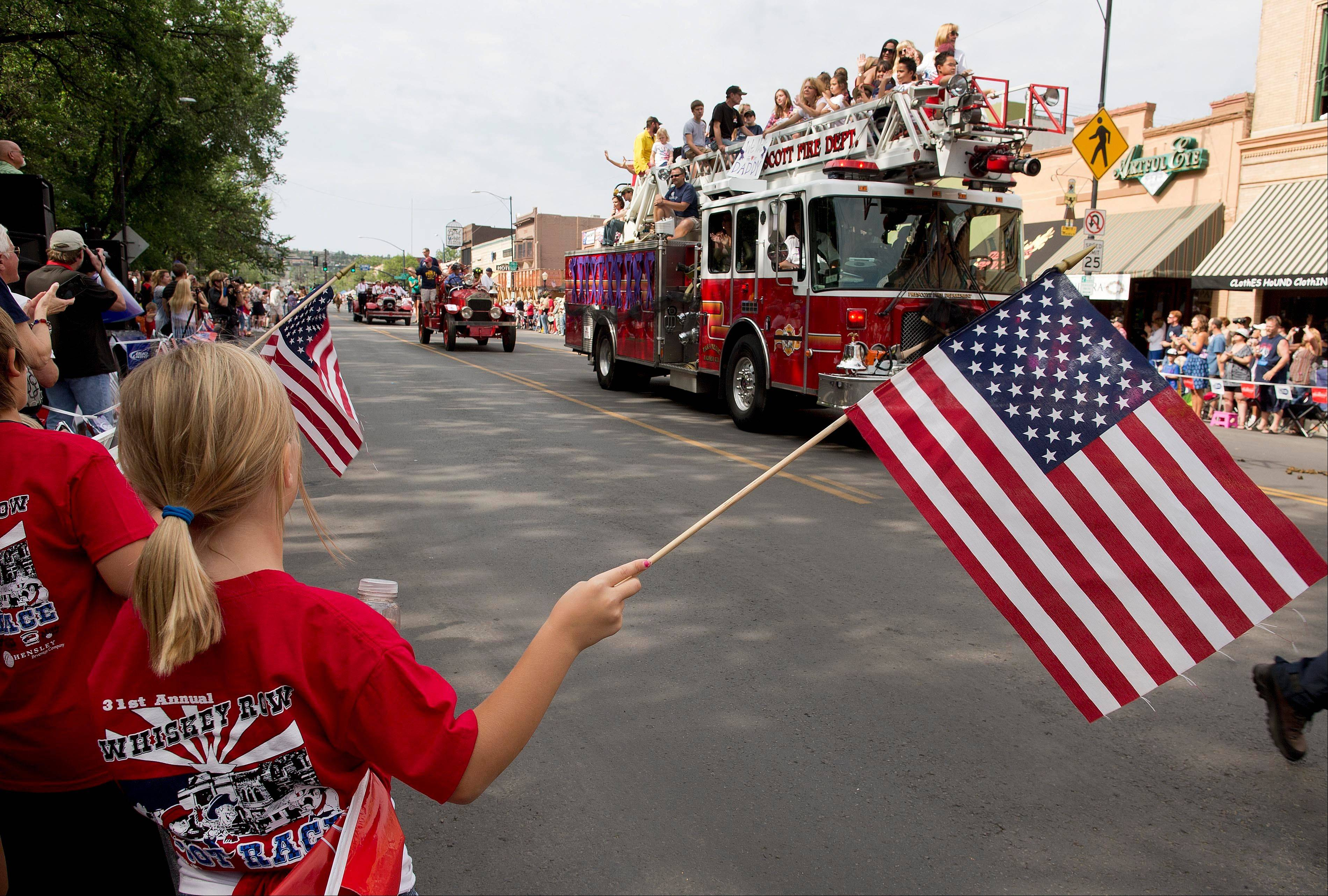 Associated Press Spectators stand as a Prescott Fire Department engine, carrying family members of the 19 fallen Granite Mountain Hotshot firefighters, slowly rolls down Montezuma Street during the Prescott Frontier Days Rodeo Parade, Saturday, July 6, in Prescott, Ariz. The procession of fire trucks started the parade to honor the Hotshots who were killed battling a blaze near Yarnell, Ariz. last week.