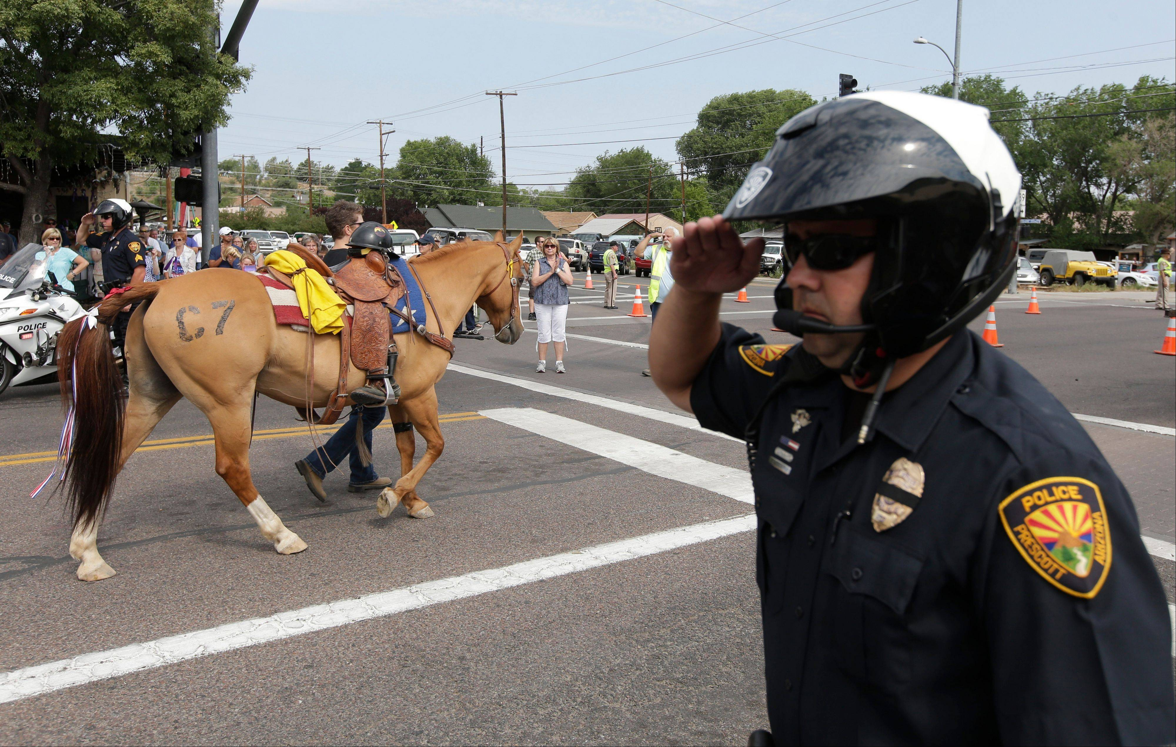 Associated Press Prescott Police Officer Todd Attenberger salutes as a riderless horse for members Granite Mountain Interagency Hotshot Crew walks in Prescott Frontier Days Rodeo Parade Saturday, July 6, in Prescott, Ariz. The firefighters were killed battling a wildfire near Yarnell, Ariz., Sunday, June 30.