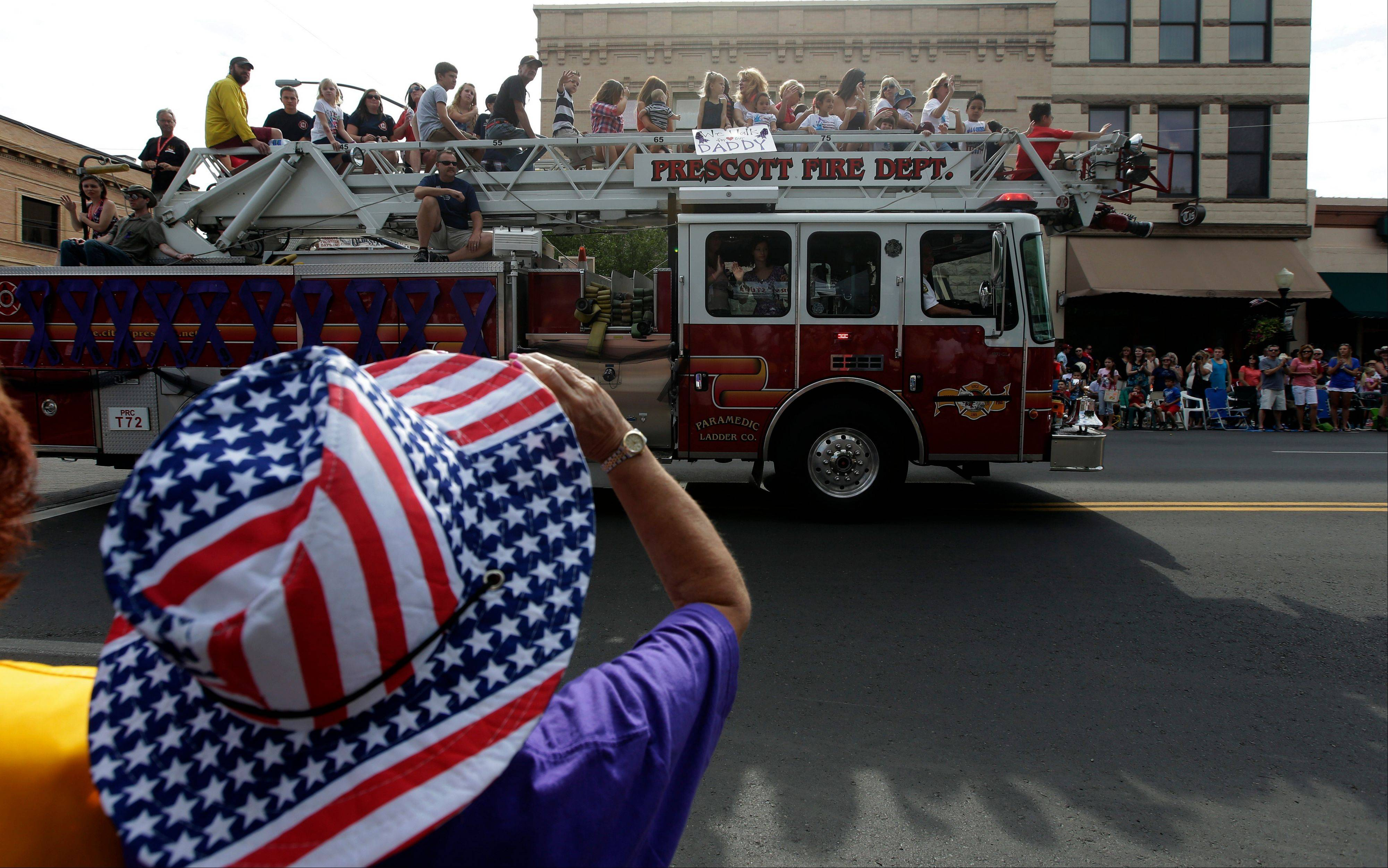 Associated PressA fire truck carrying friends and family members of the Granite Mountain Interagency Hotshot Crew leads the Prescott Frontier Days Rodeo Parade Saturday, July 6, in Prescott, Ariz. The firefighters were killed battling a wildfire near Yarnell, Ariz., Sunday, June 30.