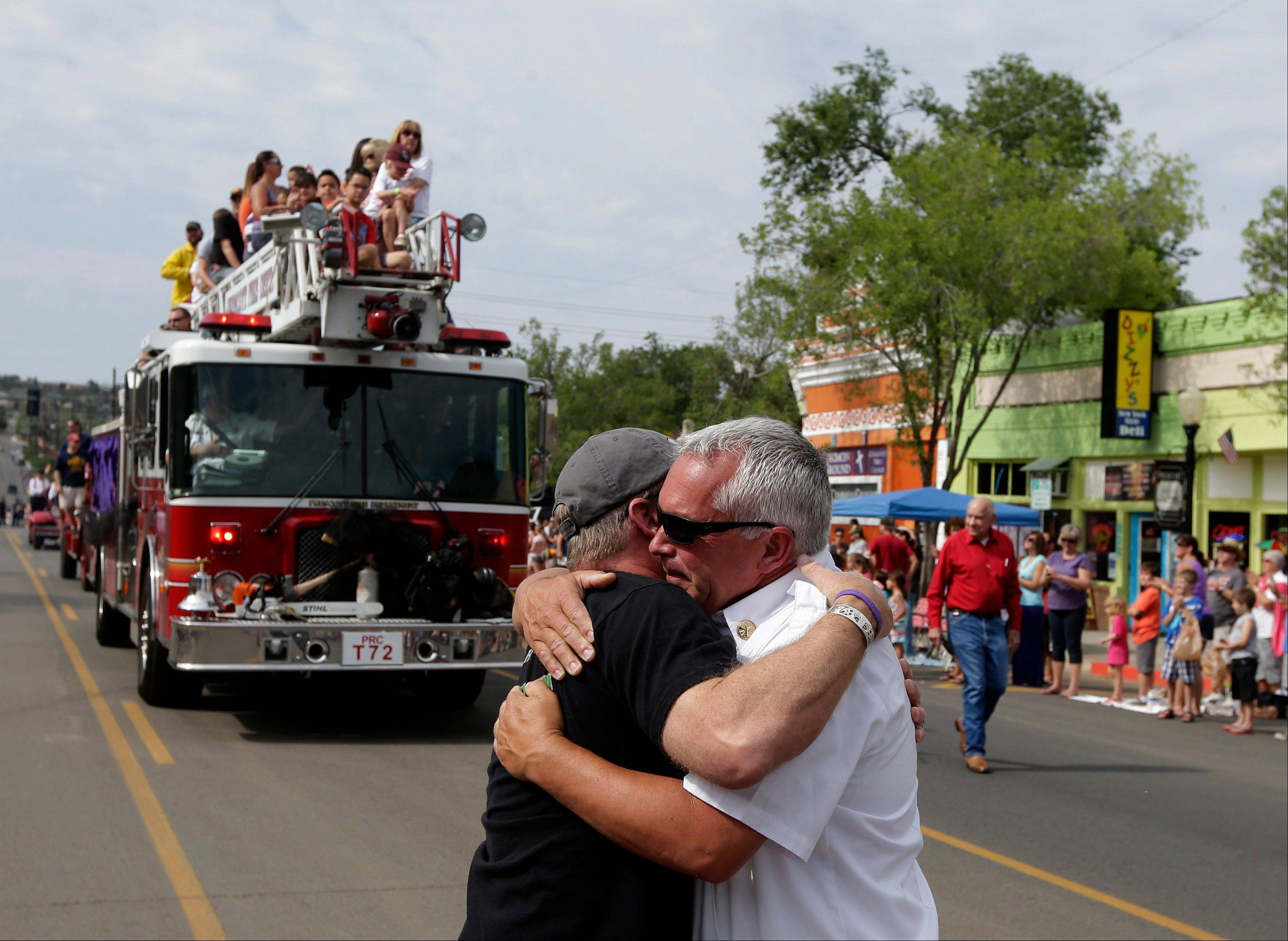 Associated PressPrescott Fire Marshal Don Devendorf, right, is hugged by Robert Gill as a fire truck carrying friends and family members of Granite Mountain Interagency Hotshot Crew rides in Prescott Frontier Days Rodeo Parade Saturday, July 6, in Prescott, Ariz. The firefighters were killed battling a wildfire near Yarnell, Ariz., Sunday, June 30.