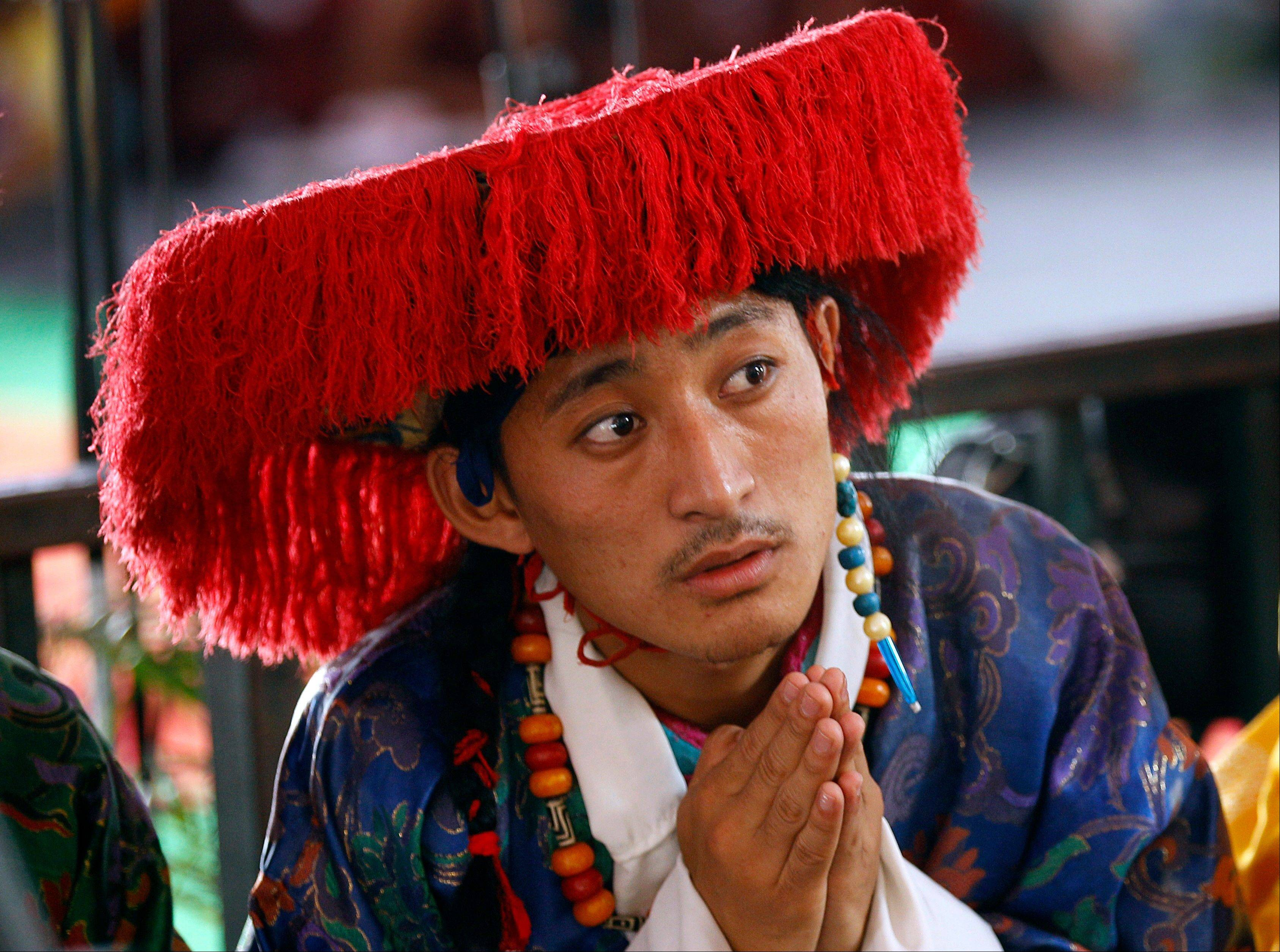 "A traditional Tibetan artist listens to spiritual leader the Dalai Lama during an event organized to celebrate the 78th birthday of the Dalai Lama at a Tibetan Buddhist monastery in Bylakuppe, about 137 miles southwest of Bangalore, India, Saturday, July 6. Speaking after an interfaith meeting, he said 150,000 Tibetans living abroad represent ""six million Tibetans (in China) who have no freedom or opportunity to express what they feel."""