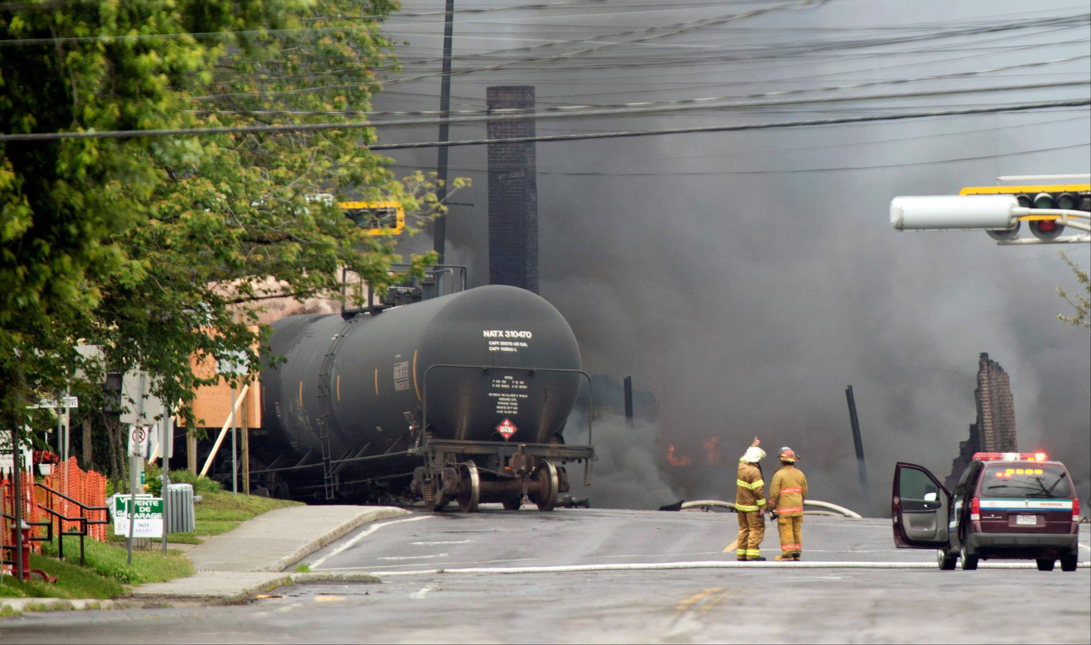 Smoke rises from railway cars that were carrying crude oil after derailing in downtown Lac Megantic, Quebec, Canada, Saturday, July 6. The derailment sparked several explosions and forced the evacuation of up to 1,000 people.