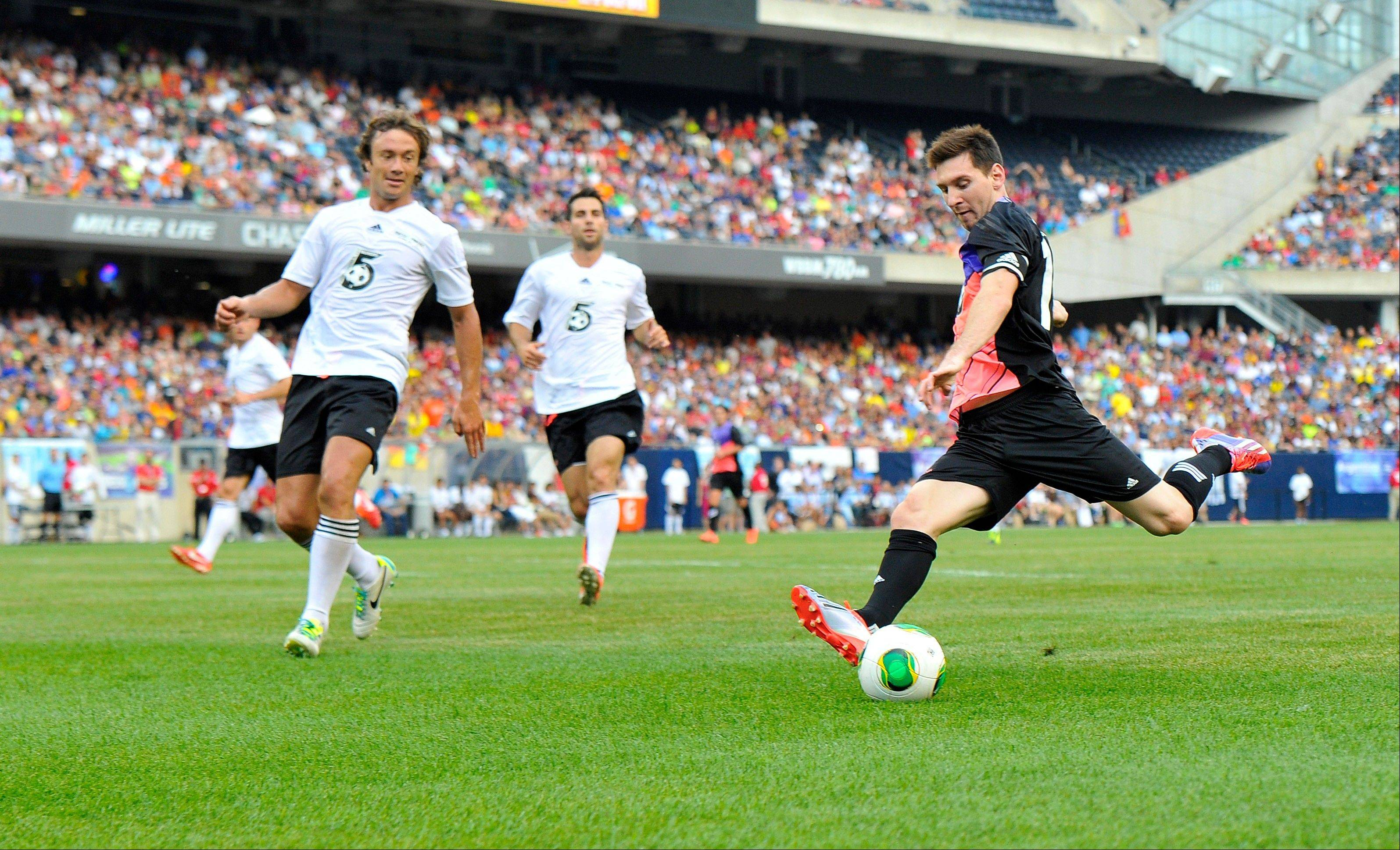 Messi's Friends' Lionel Messi, right, shoots against the Rest of the World during the first half of the Messi and Friends charity soccer exhibition, Saturday, July 6, 2013 in Chicago.