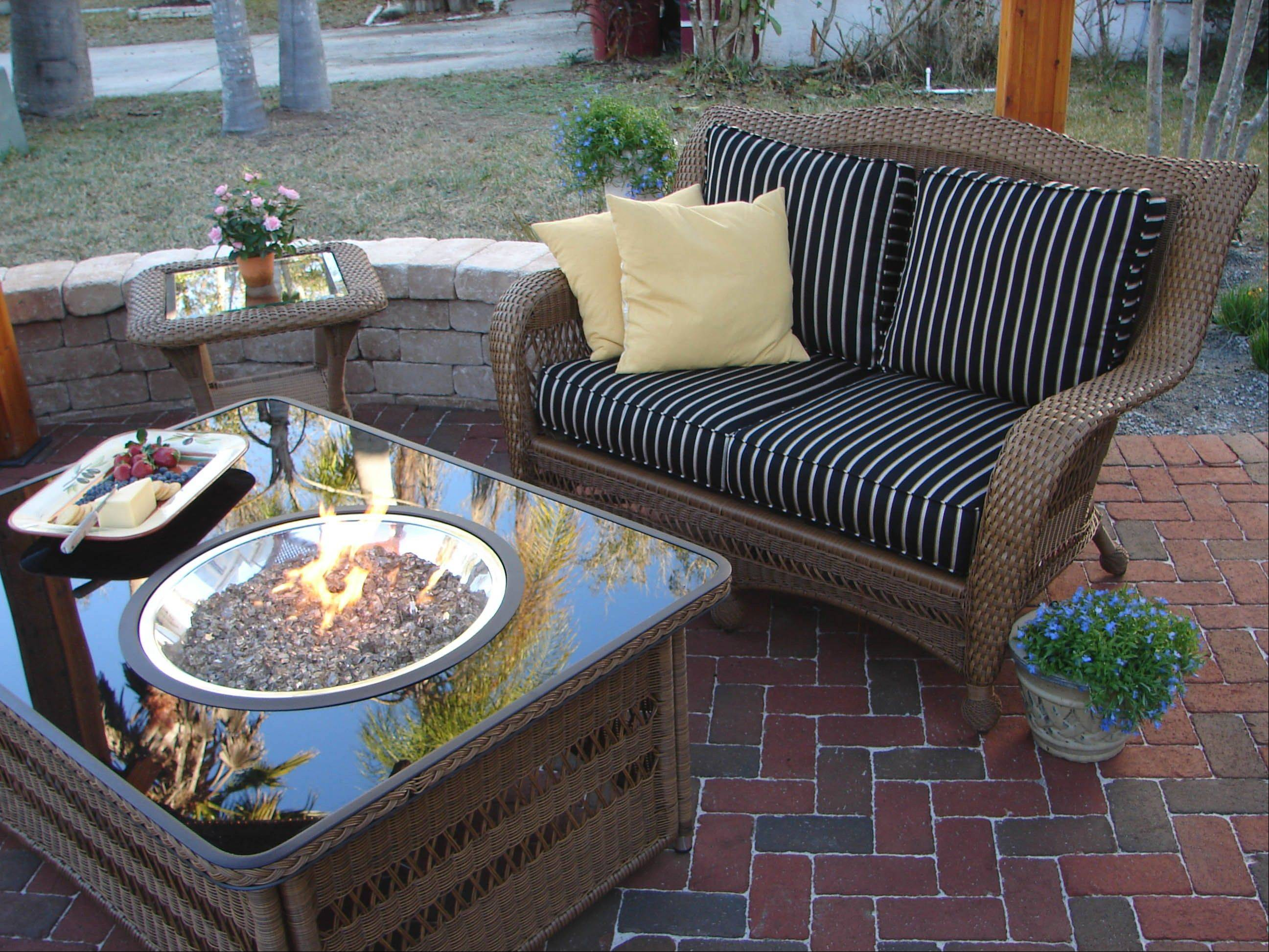 Fire pits have become upscale. This fire table is made to match the patio furniture with such features as automatic ignition and a propane tank hidden in a pullout drawer.