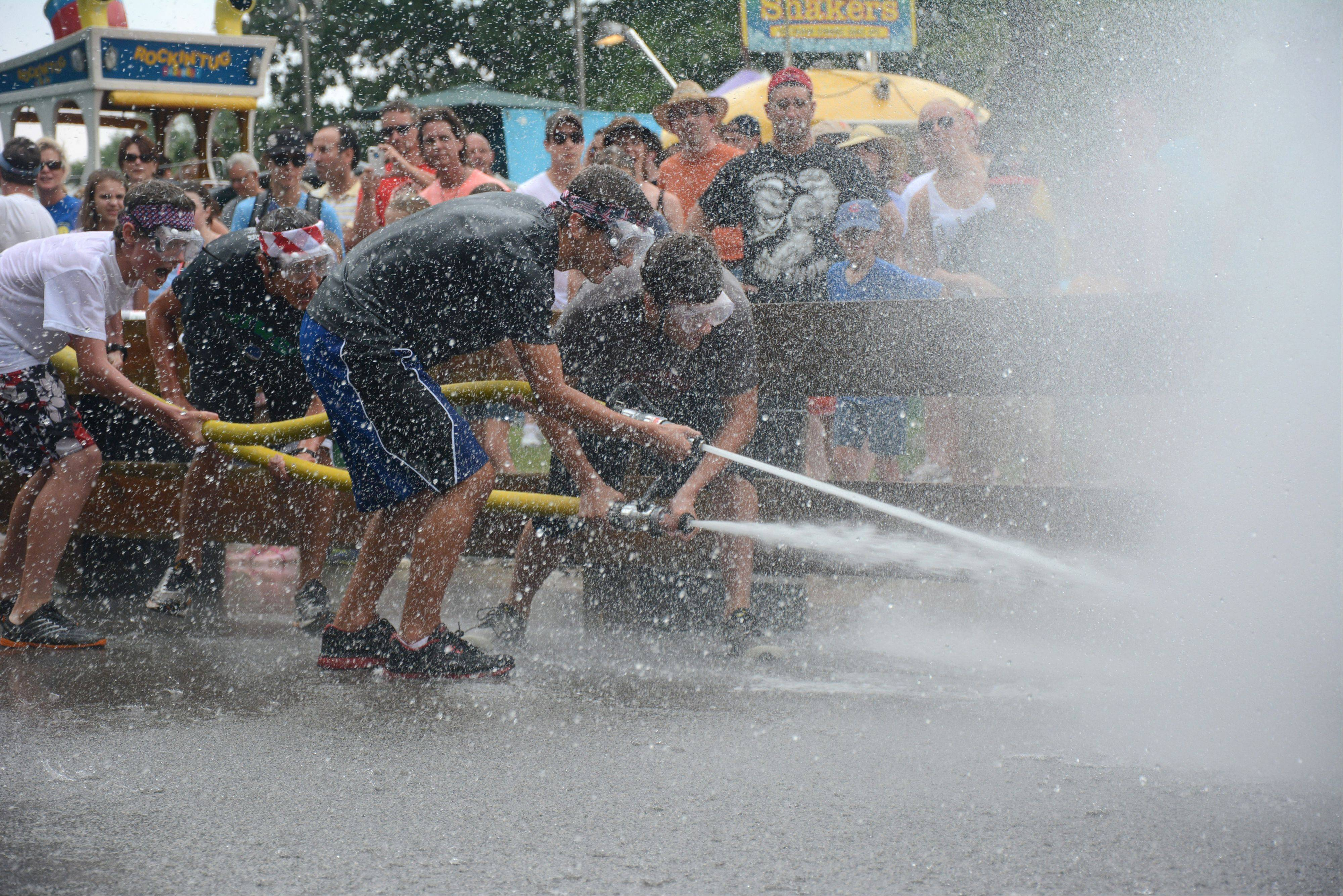 From left, Asher Ginnodo, Sam Gabriel, Nicholas Tuczak and Tyler Culliton, all of Arlington Heights, compete in a water fight Sunday during the final day of Arlington Heights' Frontier Days.