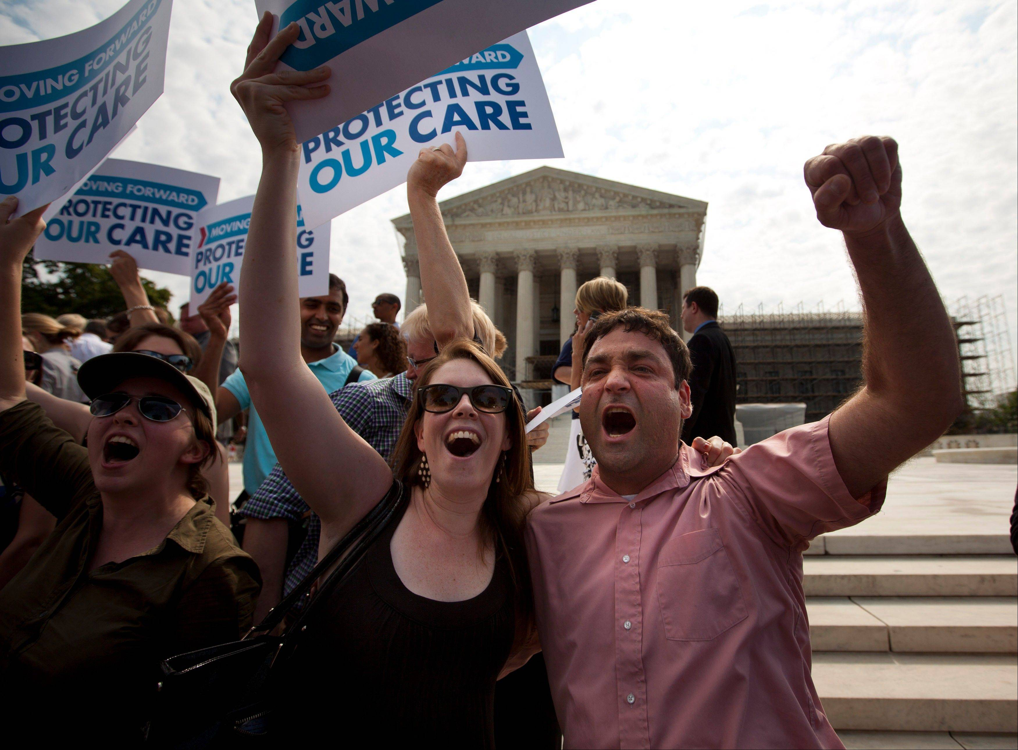 In this June 28, 2012, file photo Claire McAndrew, left, and Donny Kirsch, both of Washington, celebrate outside the Supreme Court in Washington after the high court upheld President Barack Obama's health care overhaul. Three months before uninsured people can start shopping for coverage, some big unknowns loom.