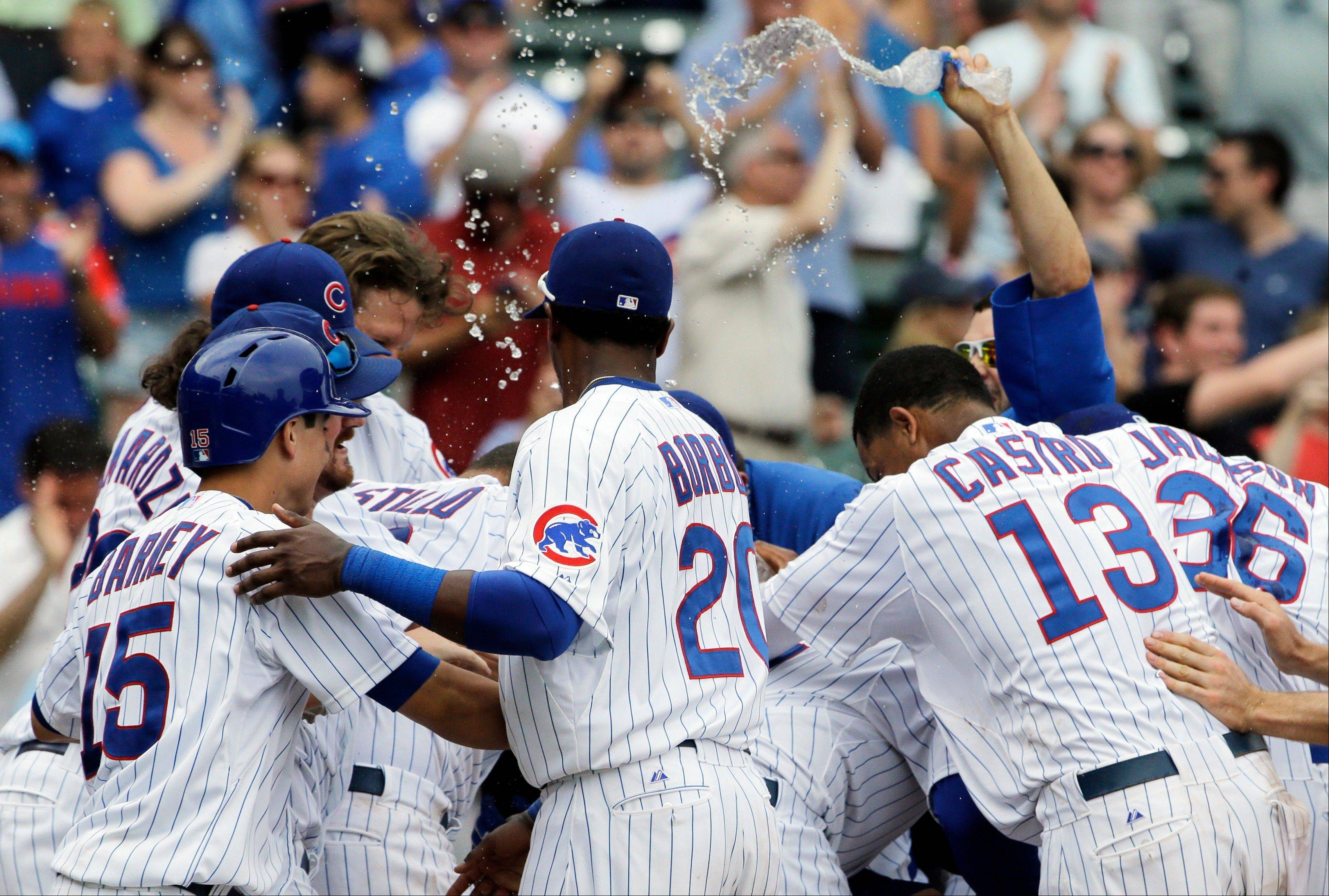 The Cubs celebrate after Dioner Navarro's sacrifice fly sunk the Pittsburgh Pirates in the 11th inning Sunday at Wrigley Field.