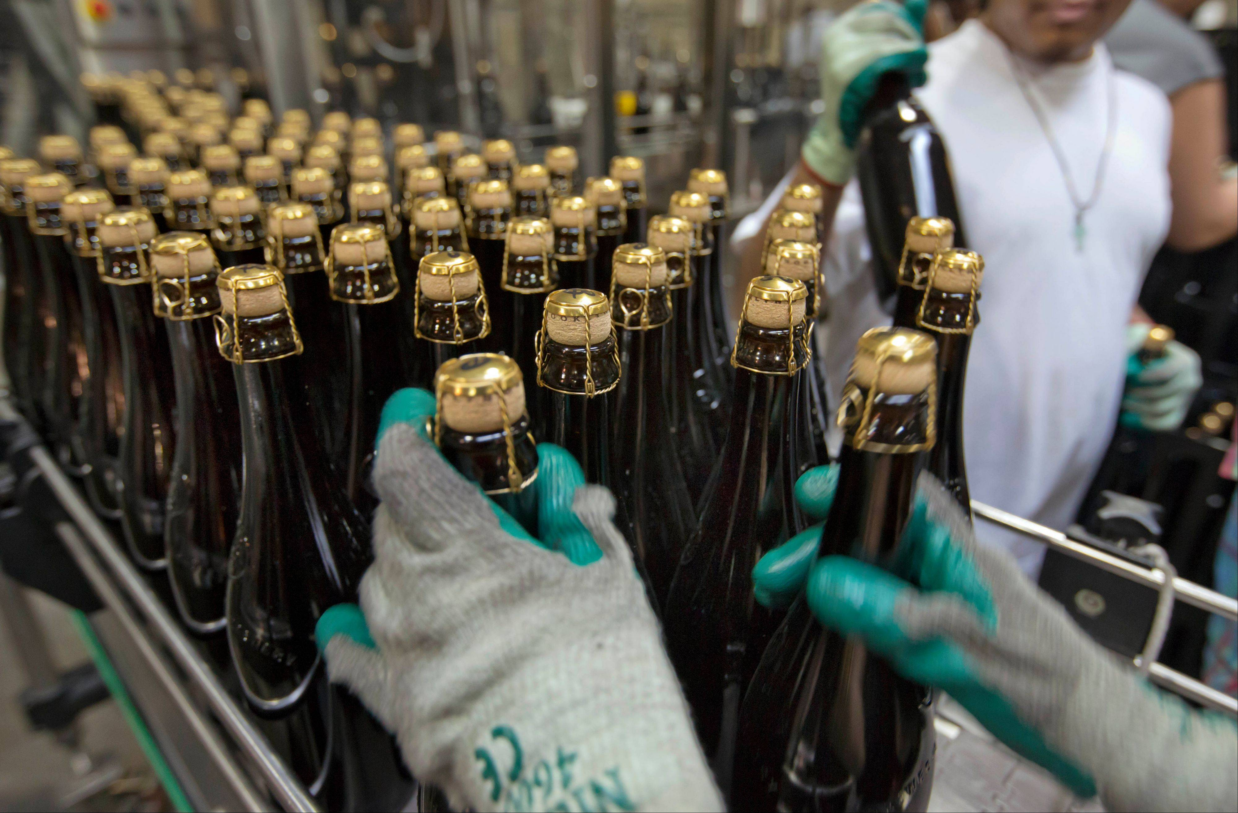In this July 1, 2013 photo, bottles of Brooklyn Local 2, a Belgian-inspired Dark Abbey Ale, are loaded on to a conveyor for labeling, at the Brooklyn Brewery, in the Williamsburg section of the Brooklyn borough of New York. In rundown urban neighborhoods across the country, craft breweries helped transform the neighborhoods around them, drawing young new residents and other small businesses.
