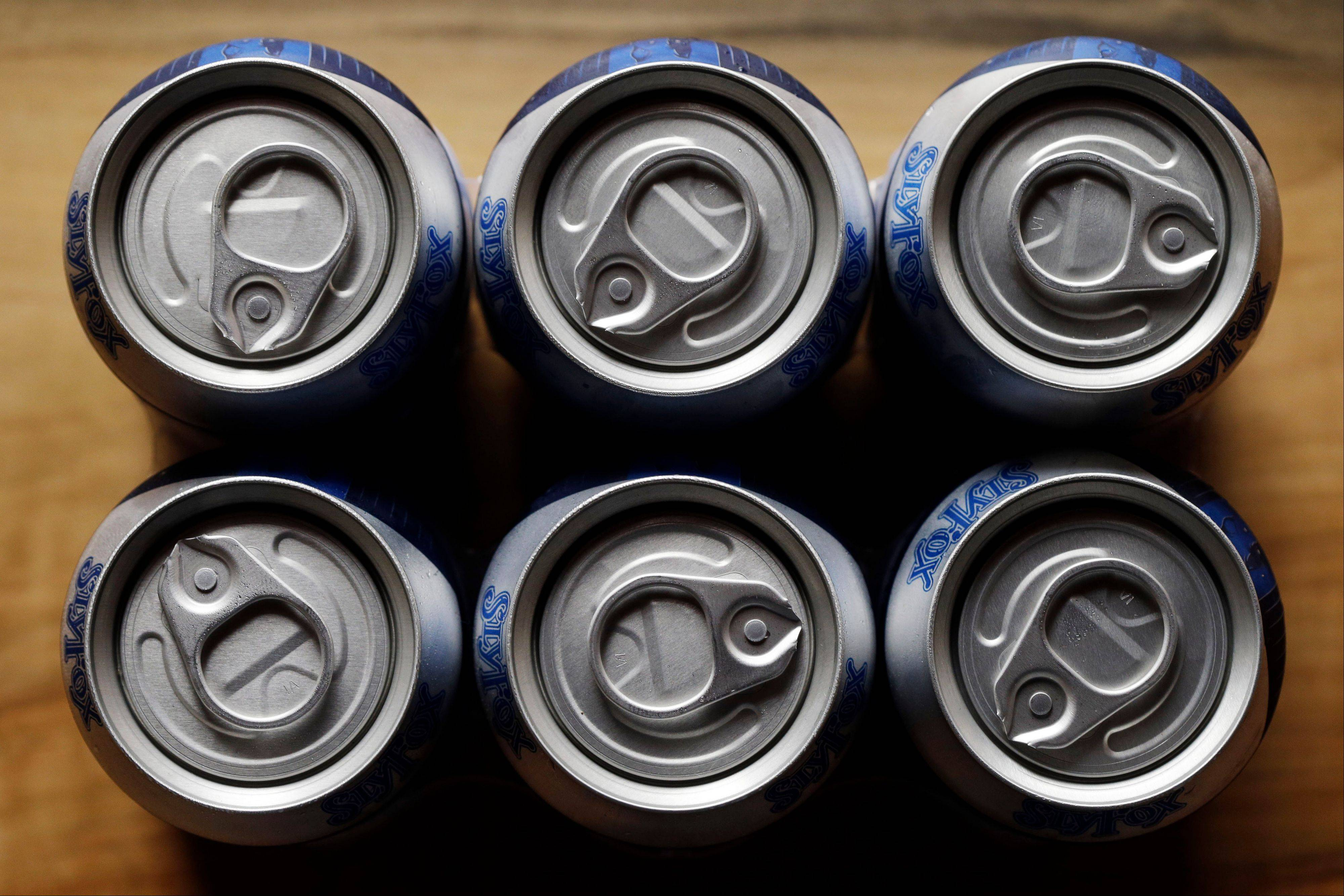 In this Monday, June 3, 2013 photo, cans of Helles Golden Lager with a 360 Lid are displayed at the Sly Fox Brewing Company, in Pottstown, Pa. Brewers and consumers debate using bottles or cans, innovation of the age-old staple continues as breweries seek to differentiate themselves on expanding beer shelves.