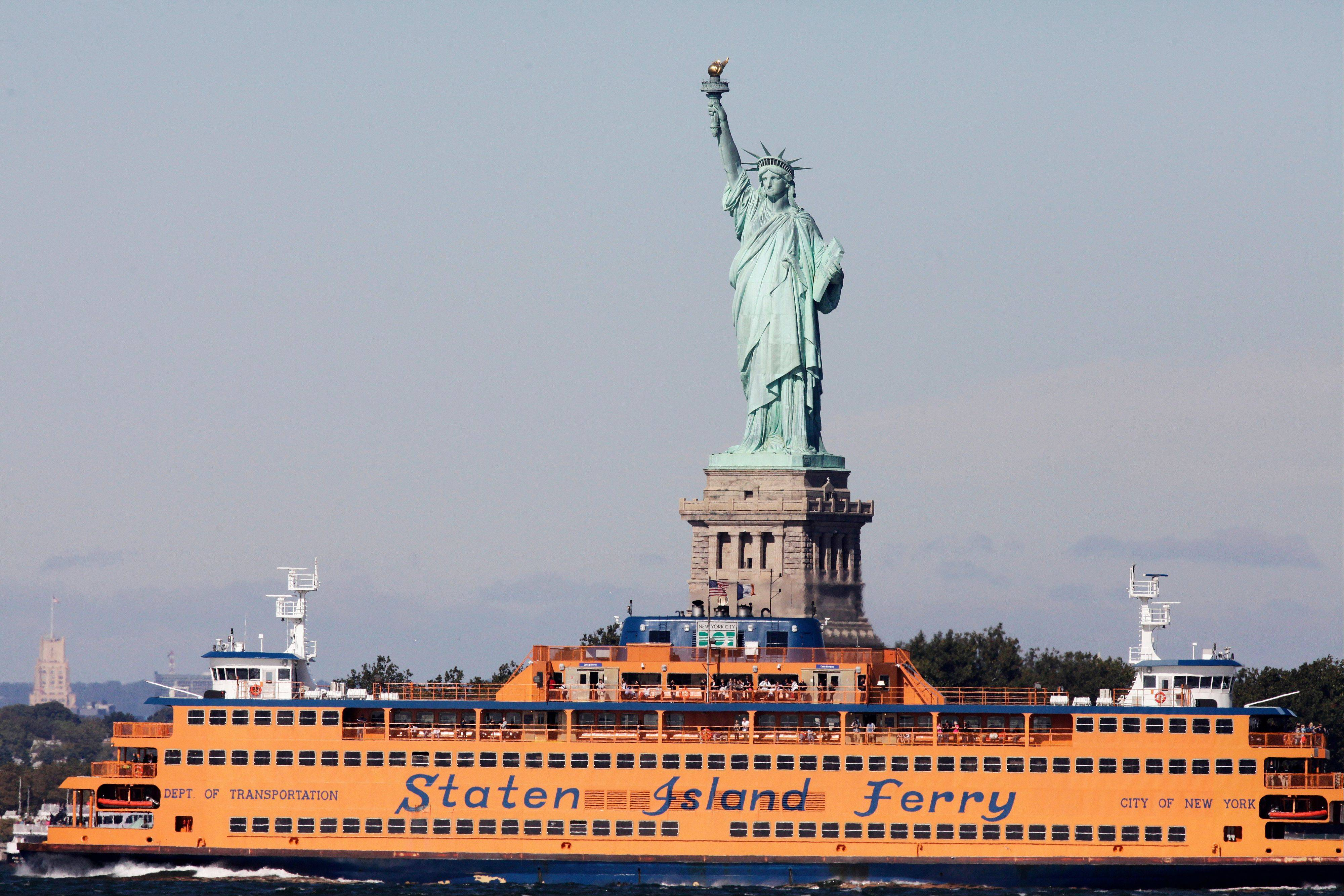 The Staten Island Ferry passes the Statue of Liberty as it crosses New York Harbor.