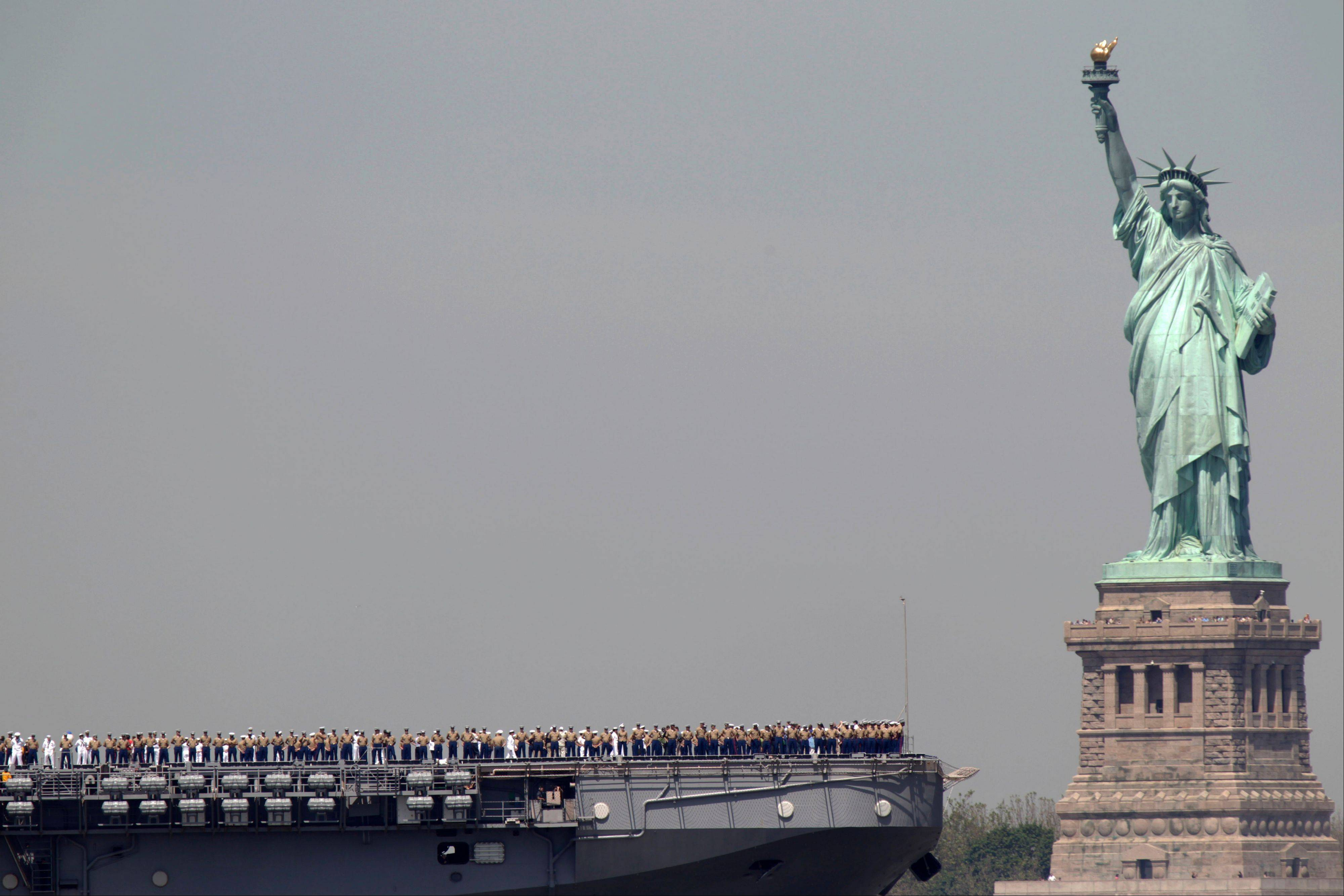 Sailors stand on the deck of the USS Iwo Jima as it passes the Statue of Liberty during Fleet Week in New York.