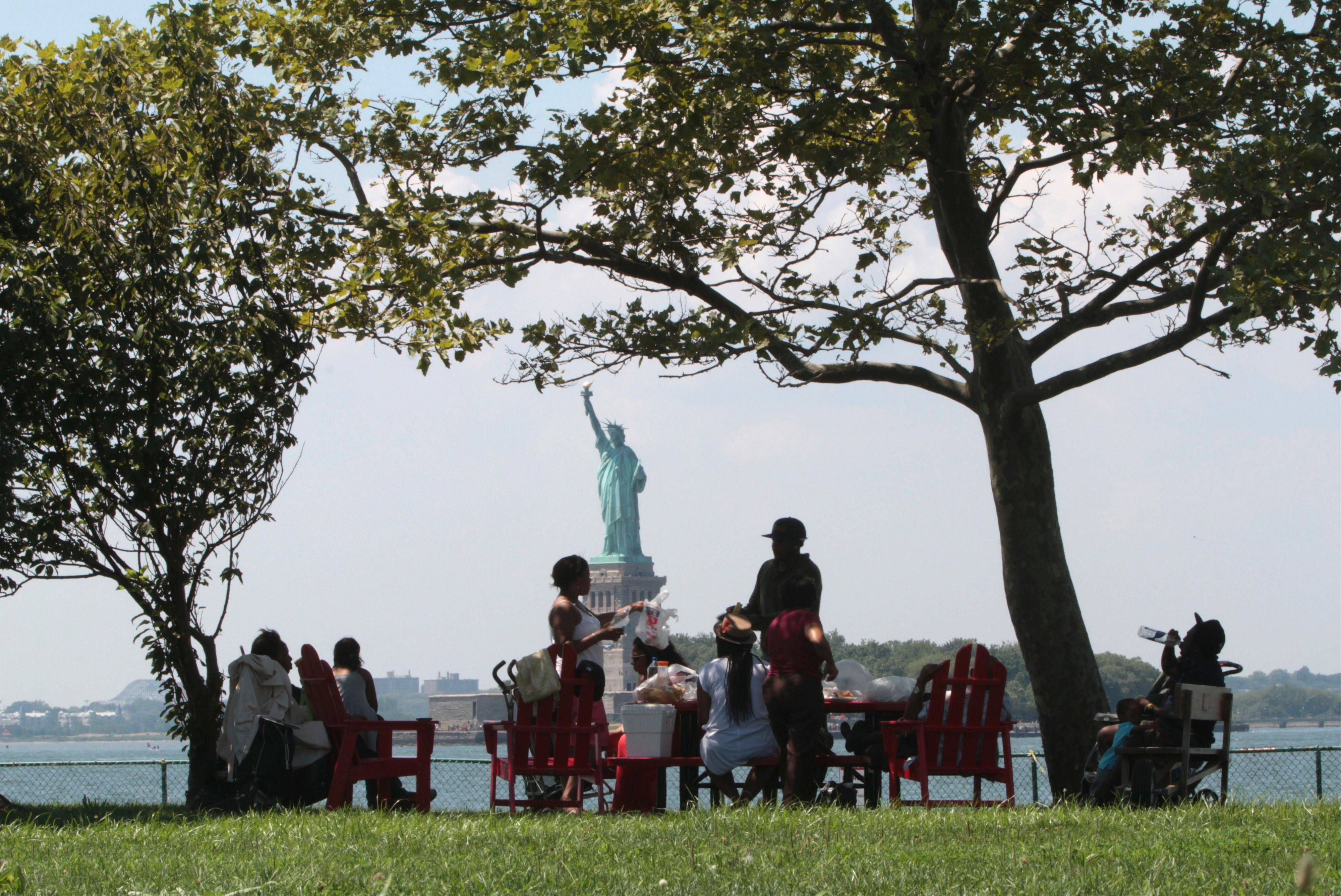 The Statue of Liberty is shown in the background as visitors to Governors Island picnic in the shade in New York.