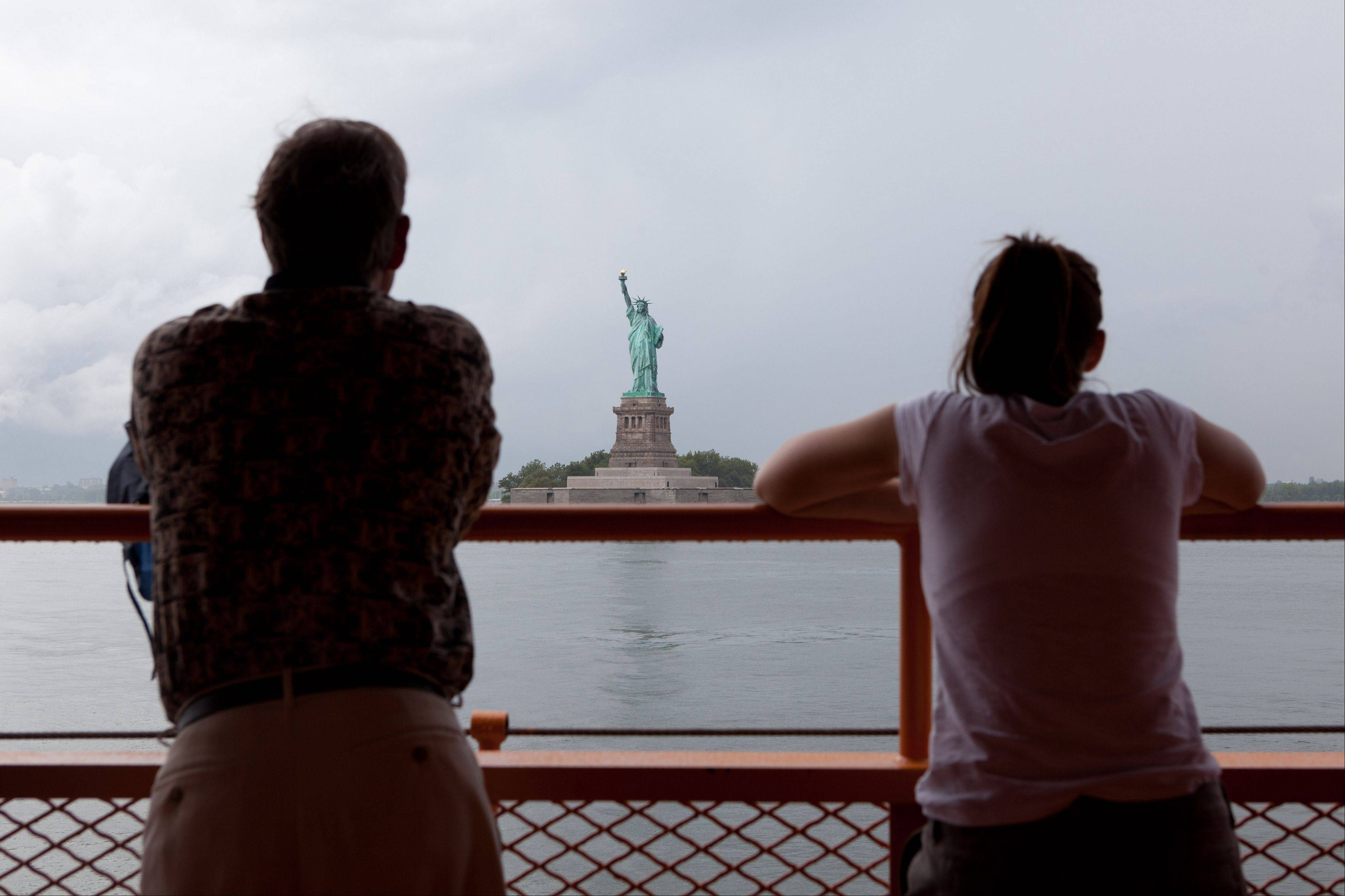 Staten Island ferry passengers look out at the Statue of Liberty in New York. The Statue of Liberty, which has been closed to visitors since Superstorm Sandy, recently reopened.