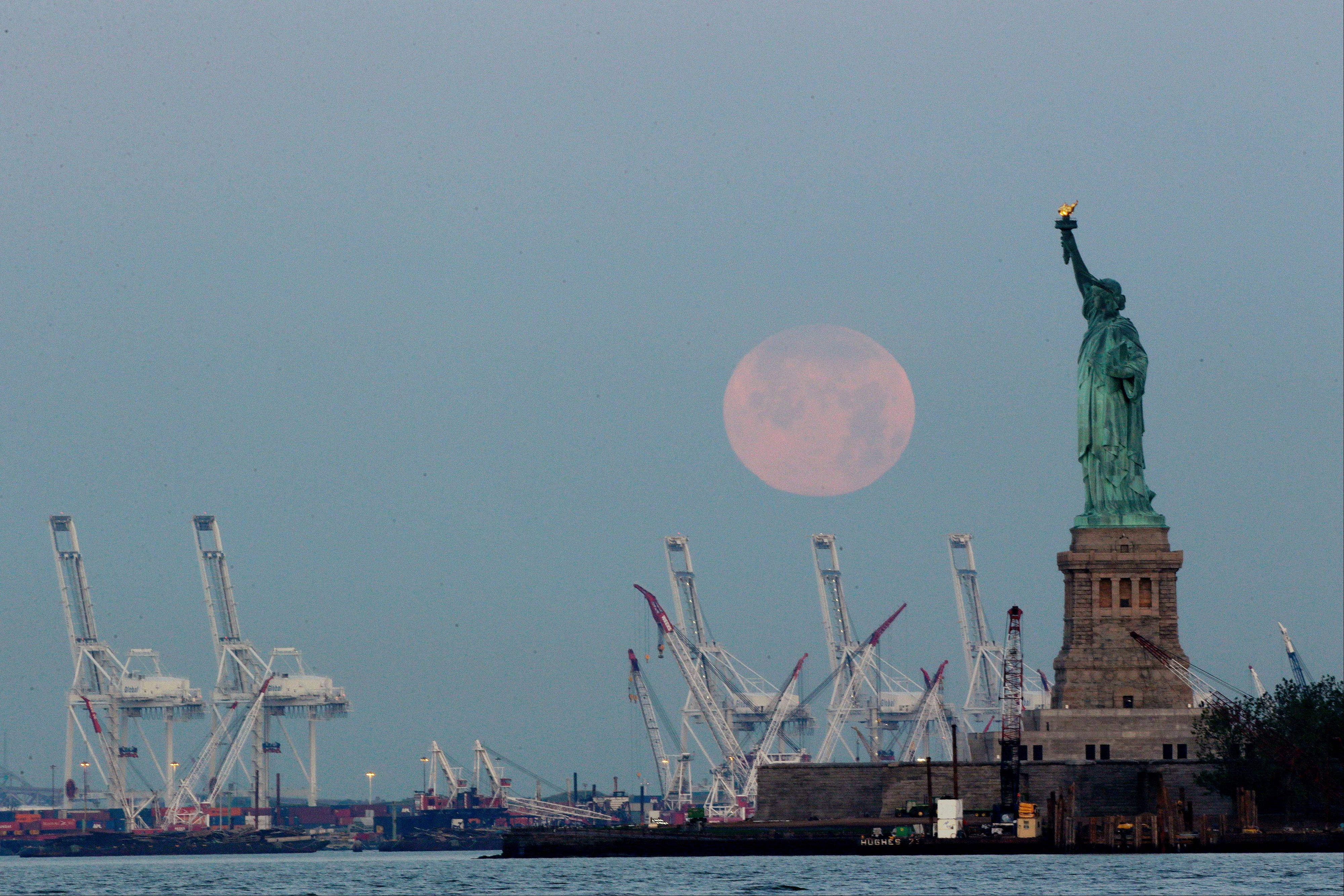 A supermoon sets near the Statue of Liberty in New York.