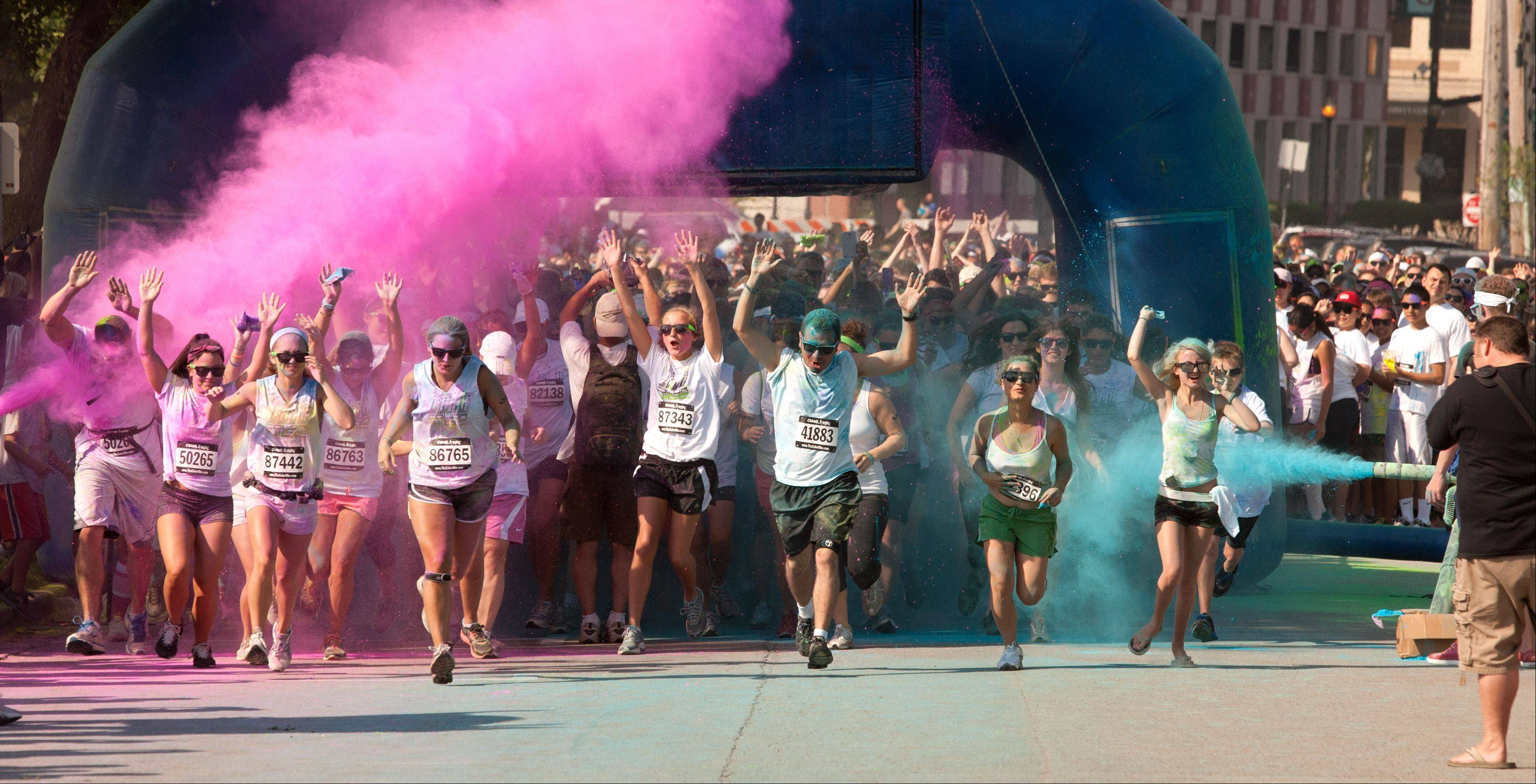 A wave of runners make their way through the starting gate of Color Vibe 5K Race along the Fox River in downtown Aurora.