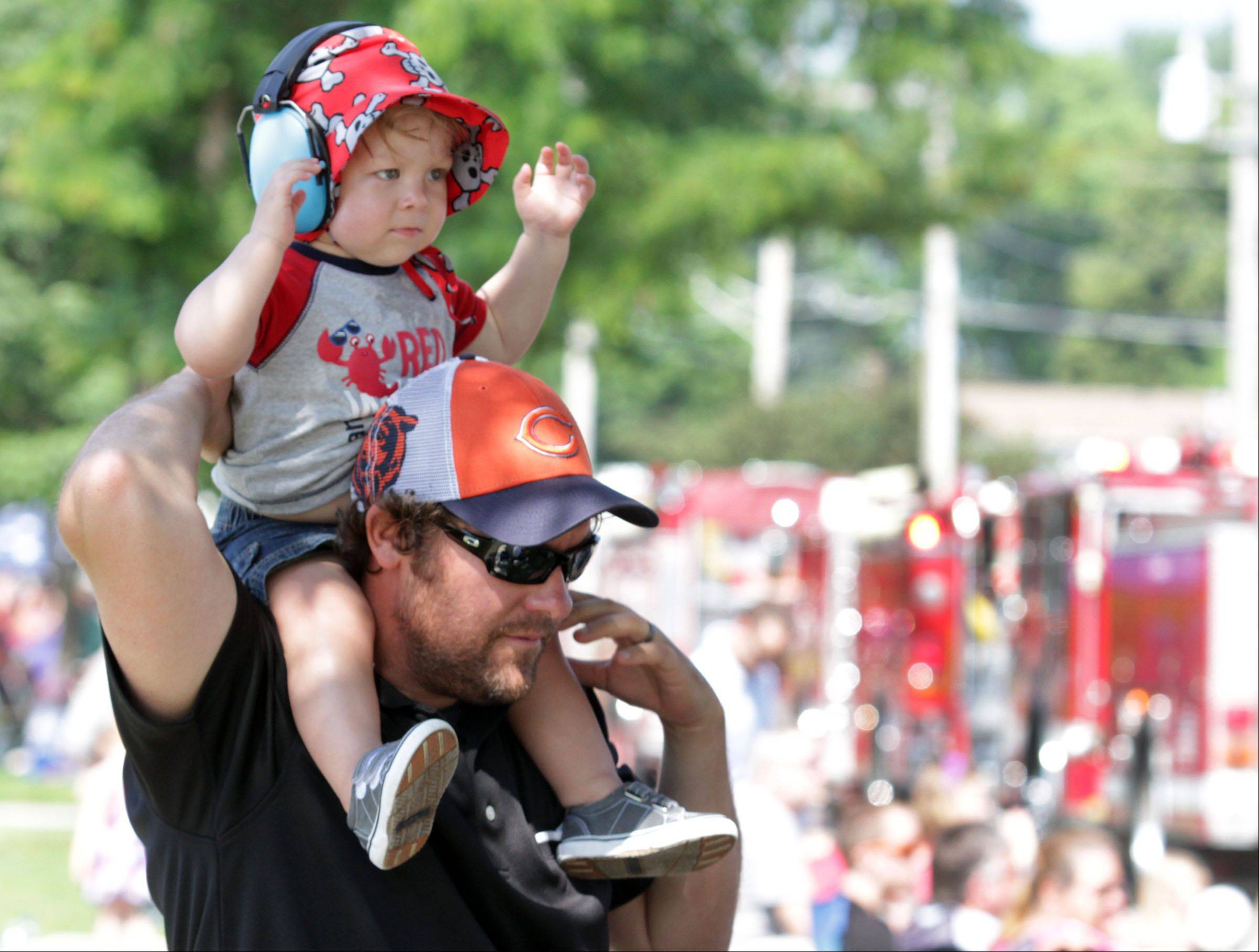 Wearing ear protection, one-year-old Brayden McNelis, on his dad Jeremy's shoulders, doesn't mind the firetruck sirens in the Celebrate Fox Lake parade on Grand Avenue Saturday.