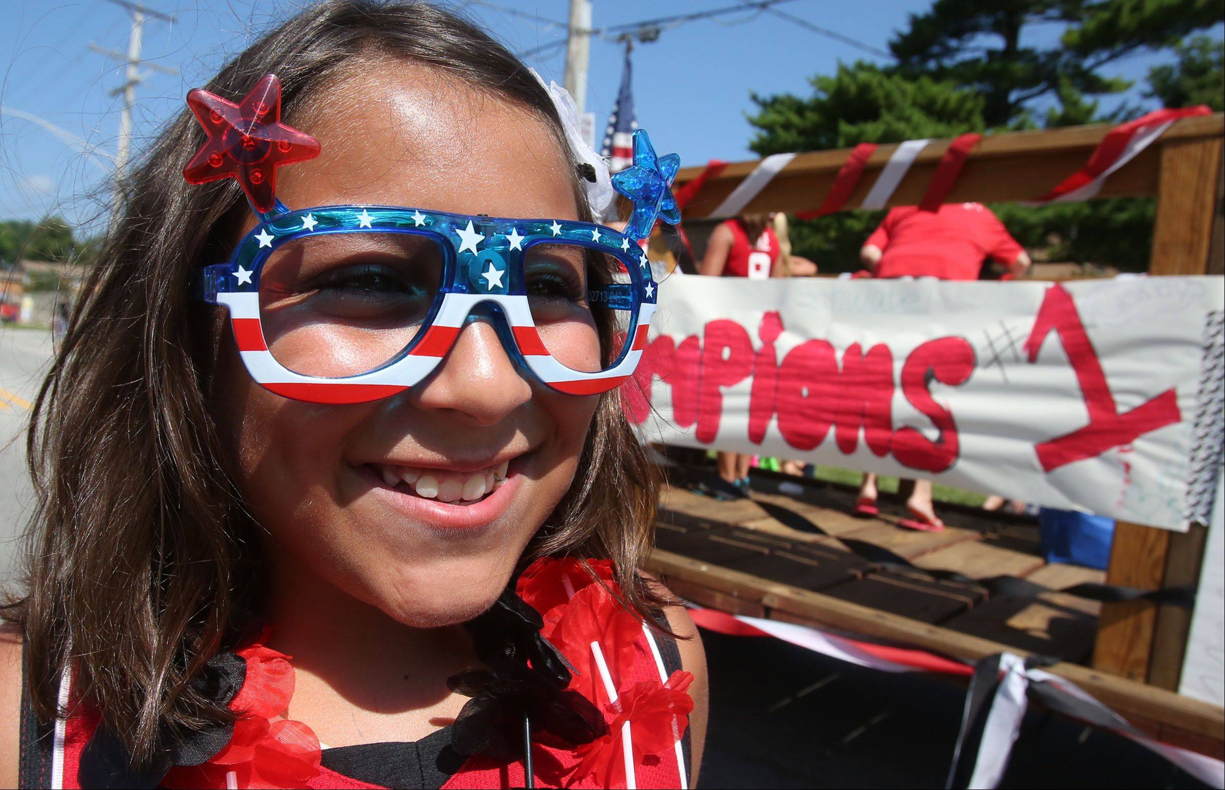 Lilliana Perez, 10, of Fox Lake, runs along side the Grant softball float in Celebrate Fox Lake parade Saturday.