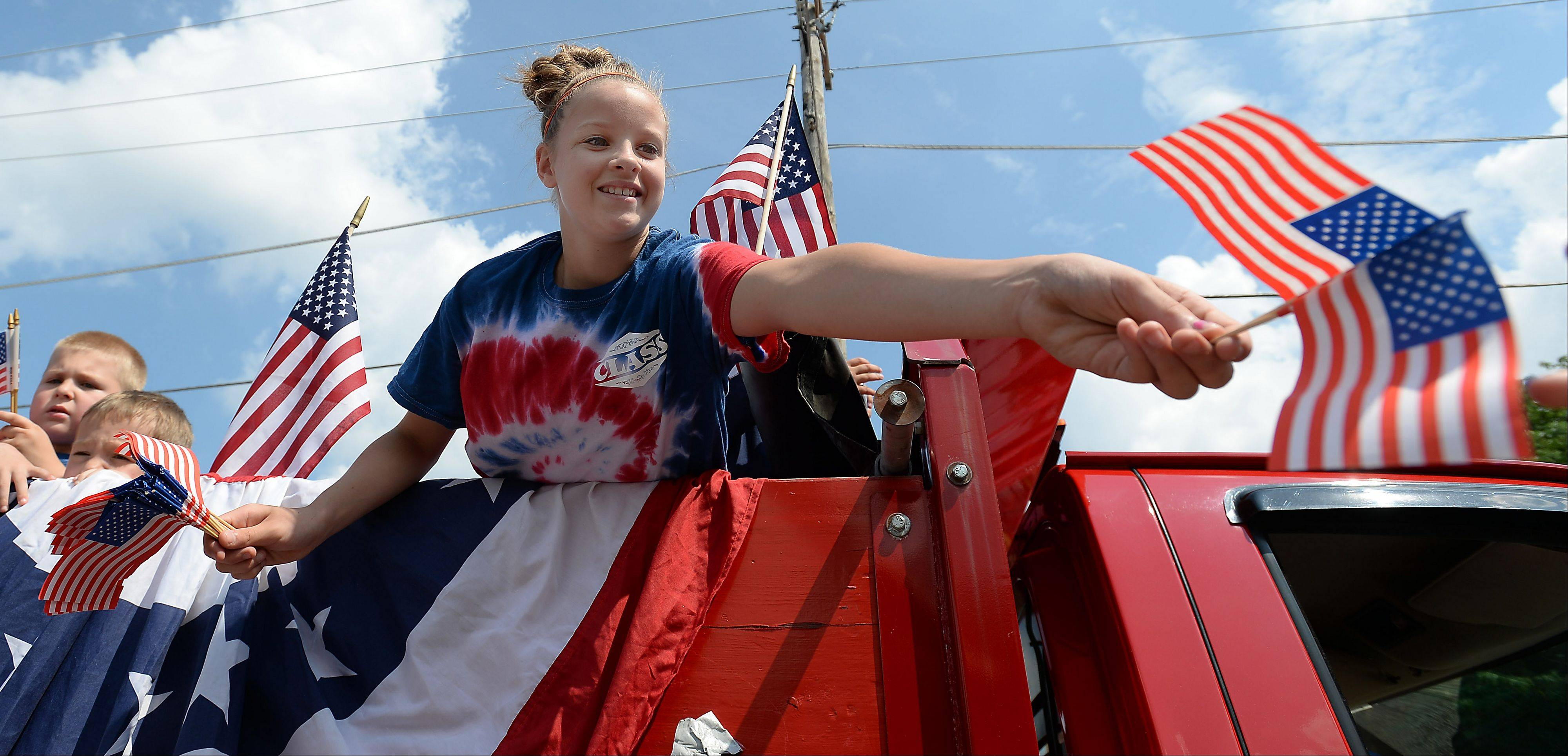 Sarah Hilliard, 13, of Rolling Meadows, hands out flags during the Palatine Fourth of July parade on Saturday.