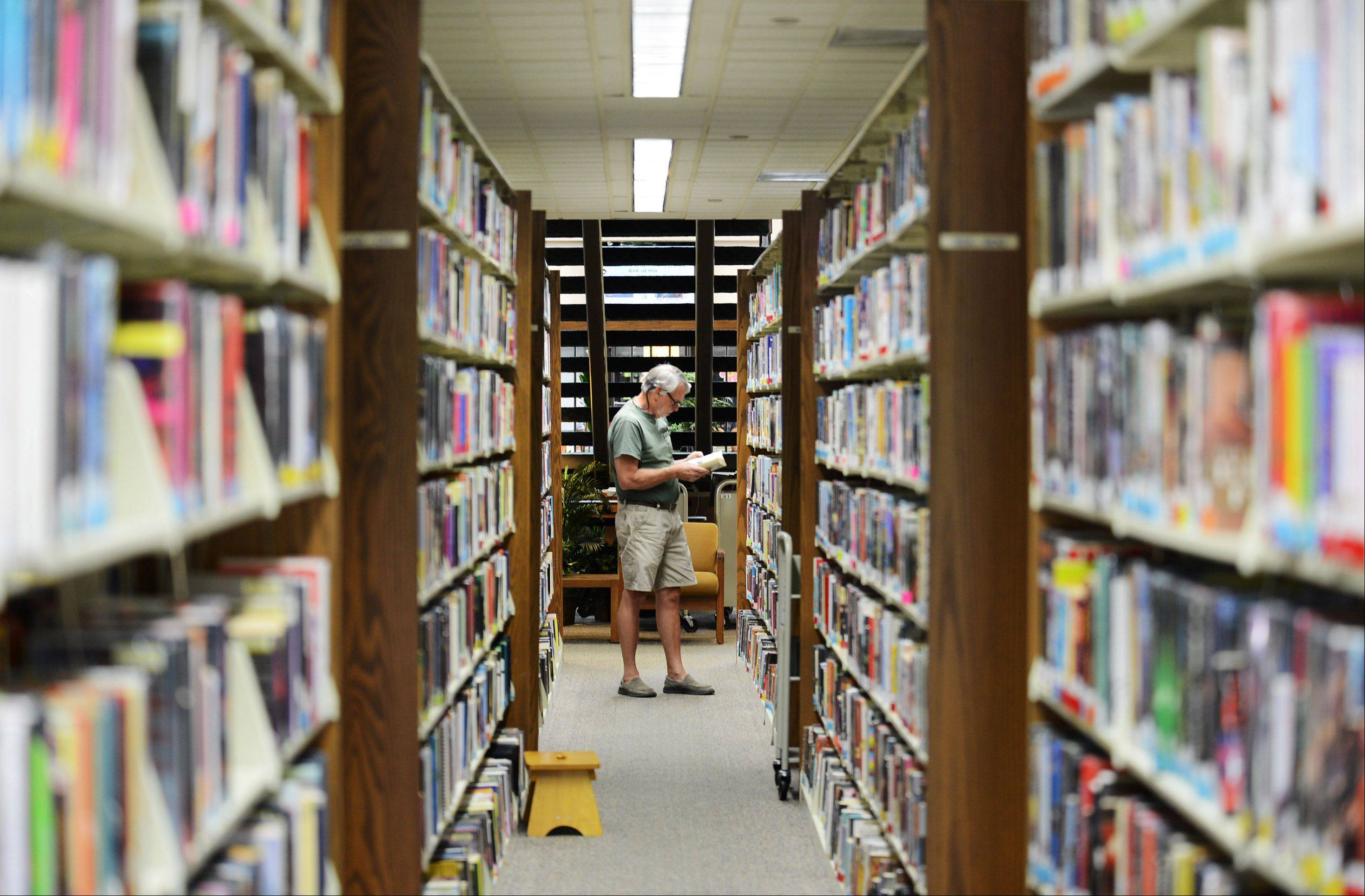 Mike Philiben, of St. Charles, looks through the selection at the St. Charles Public Library Monday. As a retiree, Mike gets to visit the library often, at least twice a week.