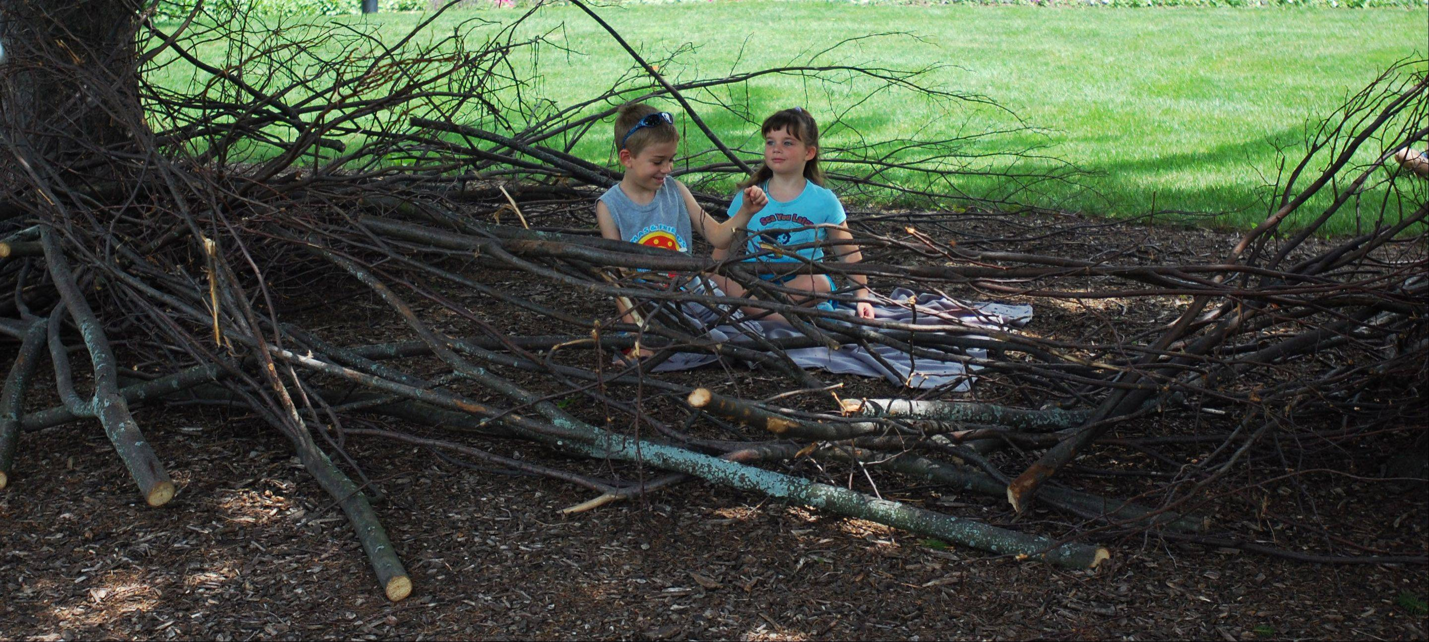 "Dax, 6, and Kate Macklin, 5, of Batavia, sit in an oversized bird nest at the ""Get Wild"" hands-on nature exploration class at Peck Farm Park in Geneva. The event runs every Saturday through August 17 and allows families to explore nature together."