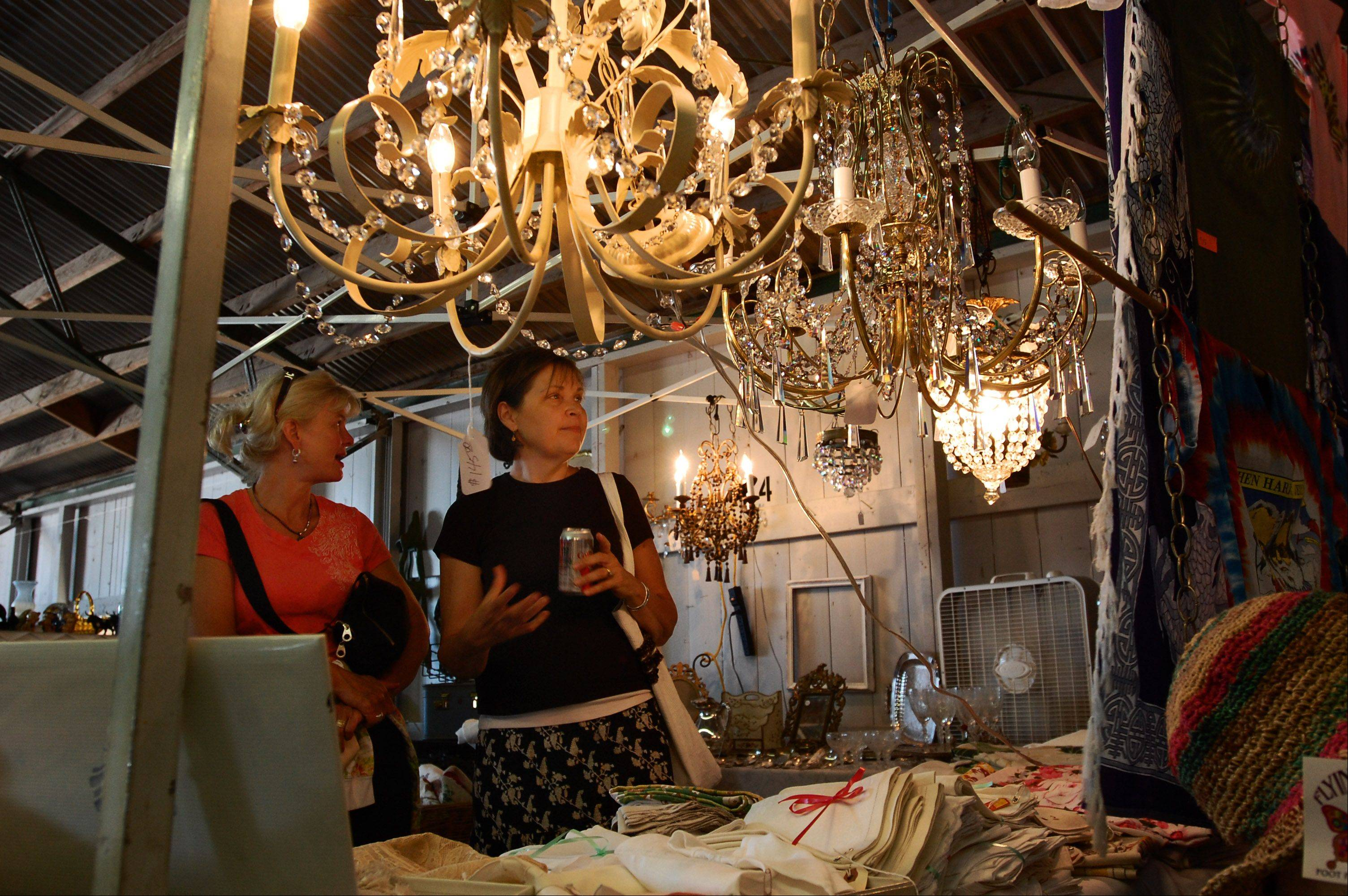 Marcia Macy and Karla Hogan, of Wheaton, look over the chandeliers at seller Dan Costantino's table Sunday at the The Kane County Flea Market. The monthly St. Charles flea market celebrates its 40th year this summer.