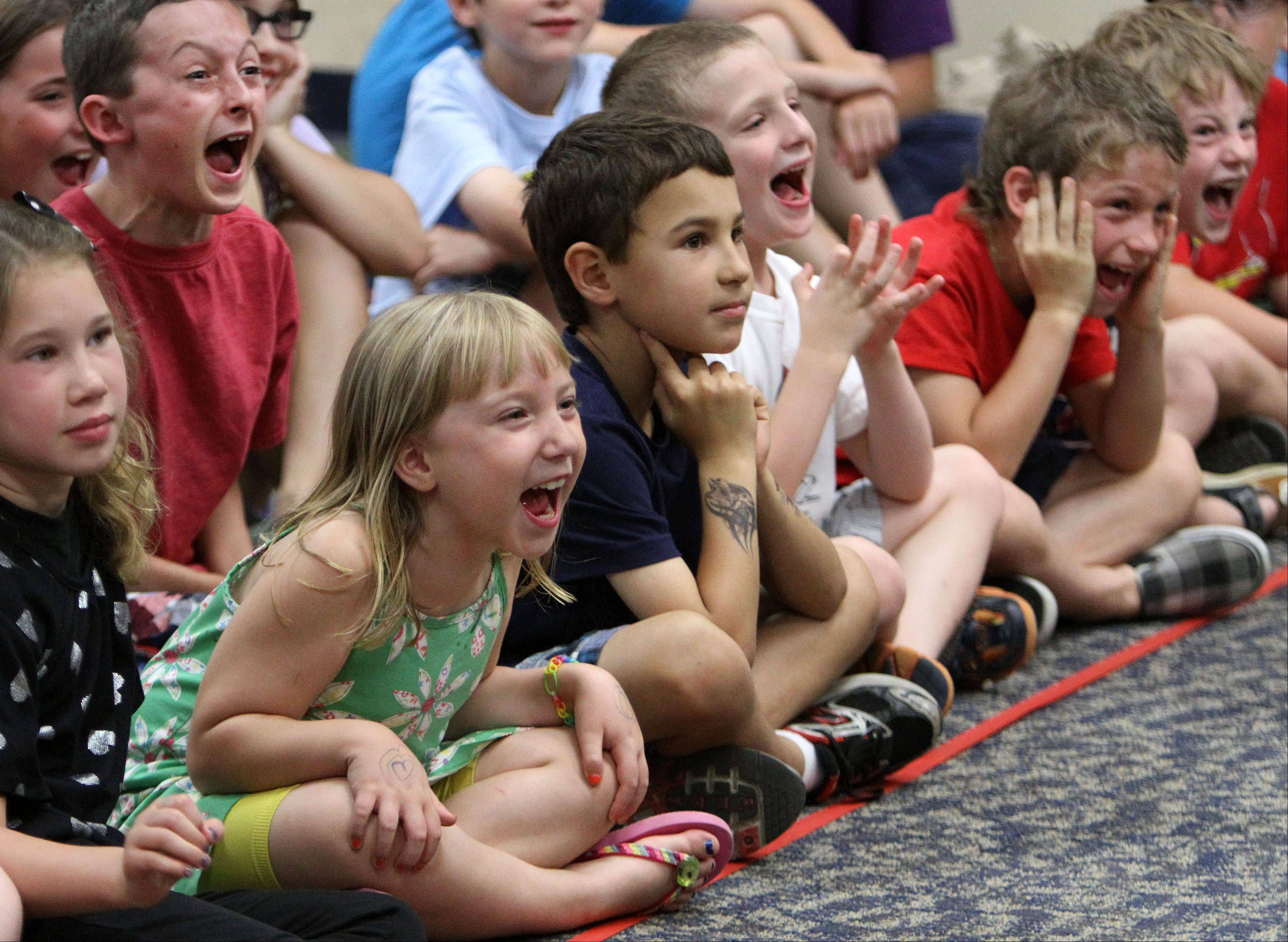 Kids react to magic tricks by Ron Clayton, A.K.A. Ron the Wizard, at Fremont Public Library Monday night in Mundelein.