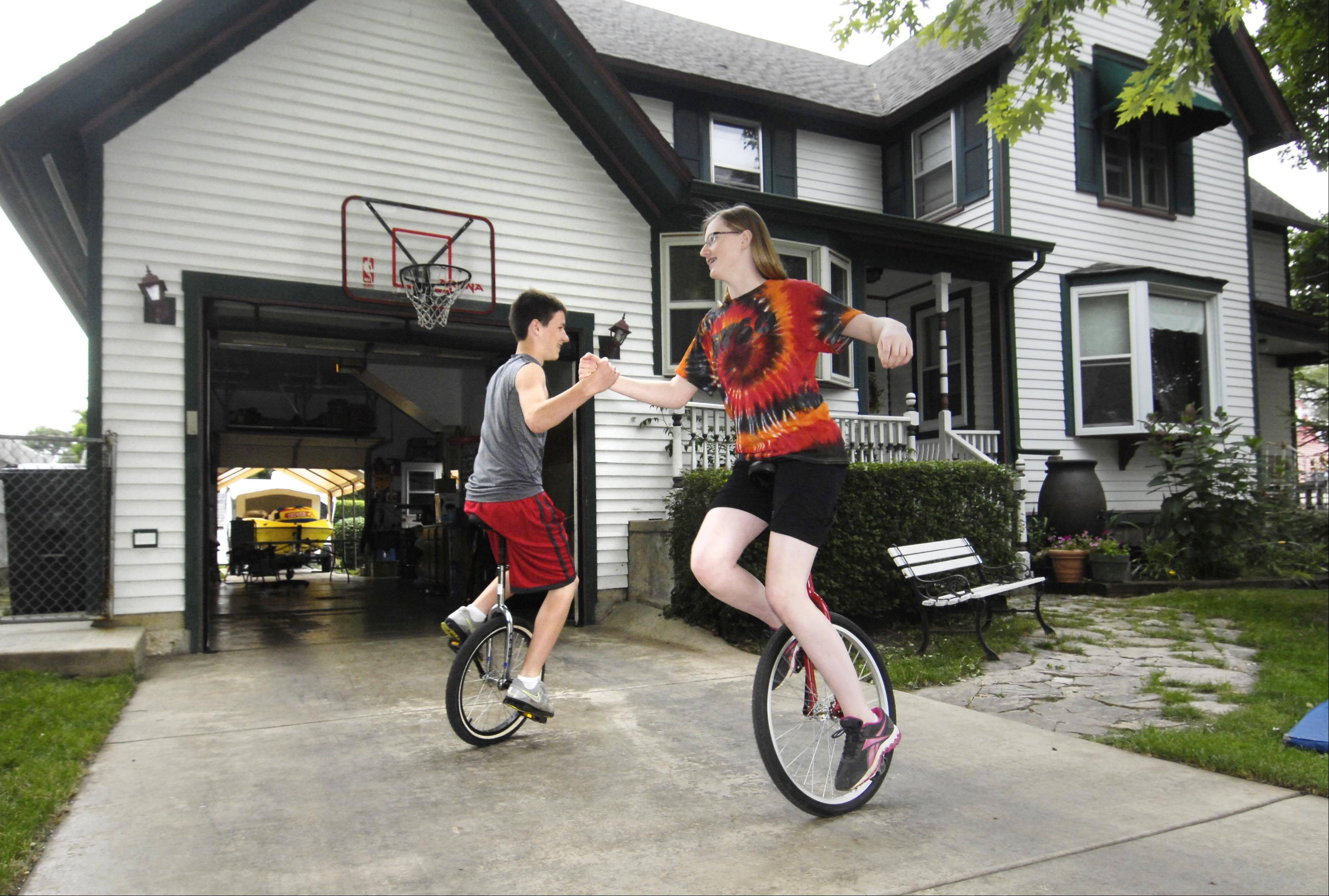 Katy Balk, 16, and her brother Nick, 14, practice a unicycle maneuver in their South Elgin driveway Tuesday afternoon. They are trying to get in shape for a two-week circus camp in Bloomington later this month.