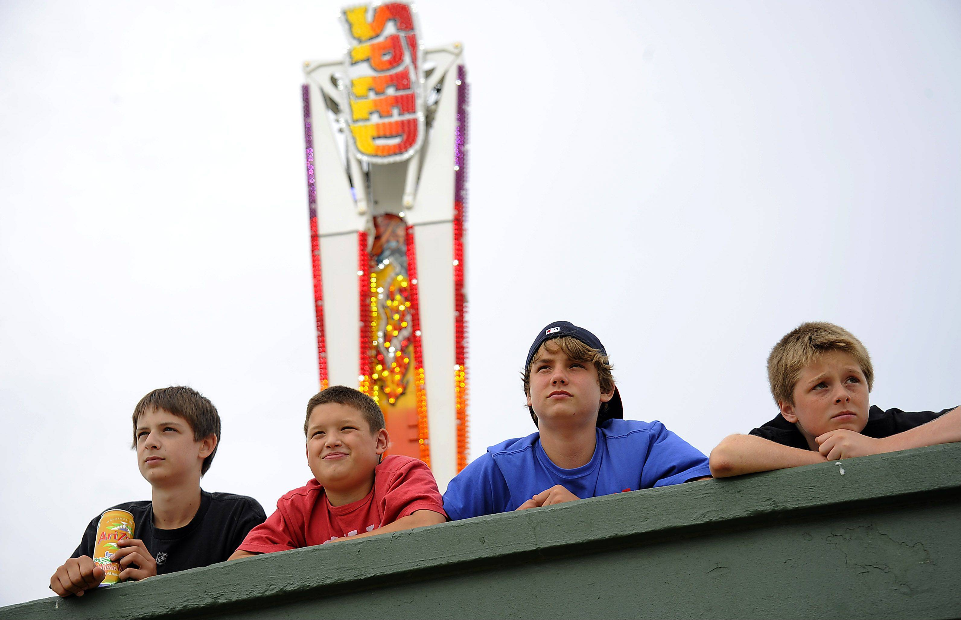 Watching the Arlington Heights Frontier days festival come to life as they lay on a baseball dugout are Kevin Donohue, 13, Jace O'Hara, 12, Riley Rundquist, 12, and Joey Belmonte, 12, all of Arlington Heights. The workers were putting the rides together for 4th of July activities.