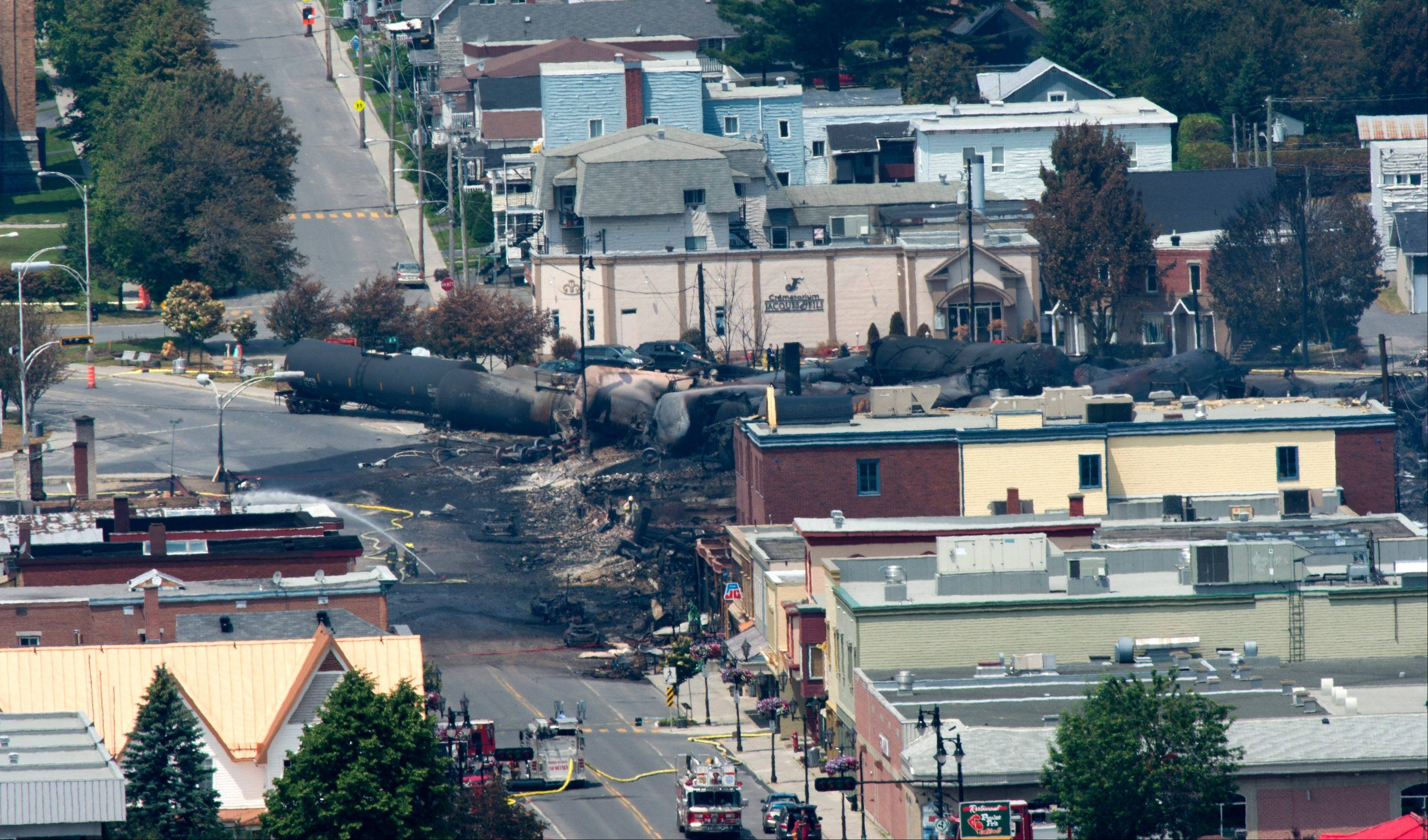 Hazardous conditions hindered firefighters' attempts Monday to search for some 40 people still missing in downtown Lac Megantic, Quebec, after a runaway oil tanker train exploded over the weekend, killing at least five people, officials said.