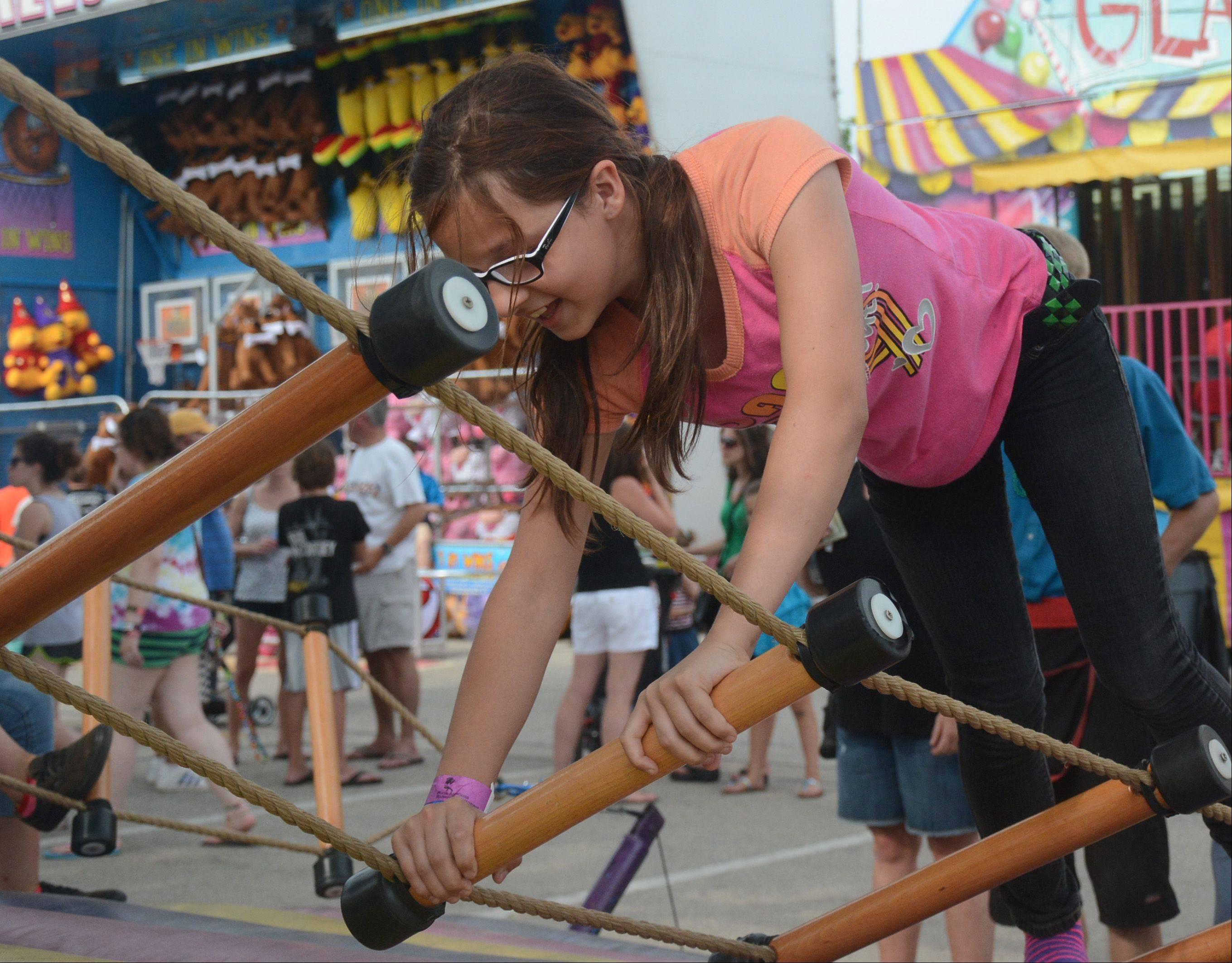 Brianna Thompson, of Arlington Heights, attempts the tilt ladder Sunday at Arlington Heights Frontier Days.