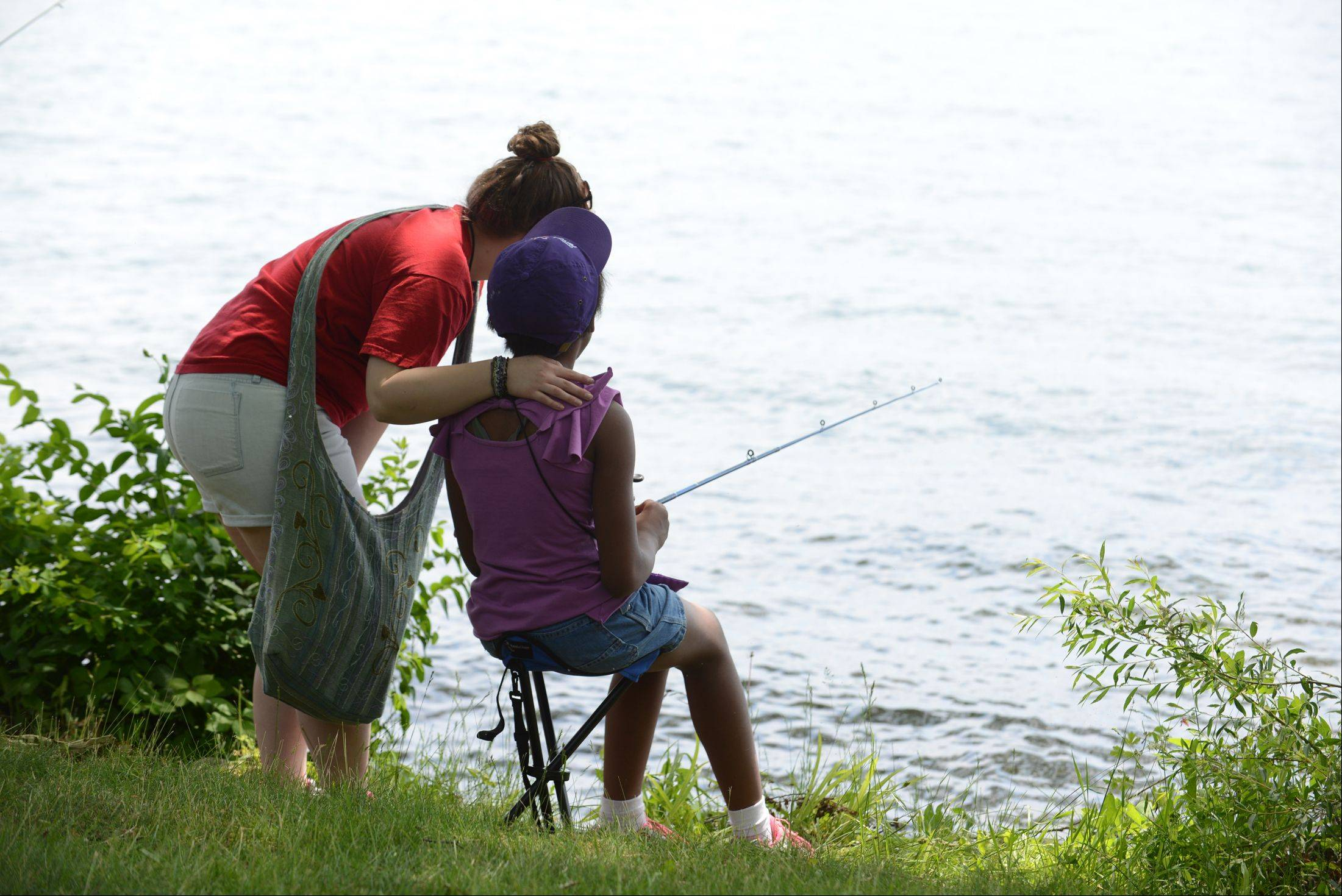 Royal Family Kids Camp counselor Amber Blaskoski of St. Charles fishes with a camper at the Wisconsin camp.