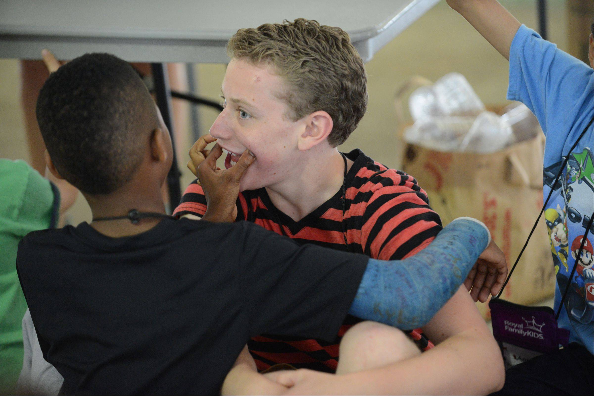A Royal Family Kids Camp camper tries to put a smile on counselor Andy Kruse's face during camp. Andy is from Batavia.