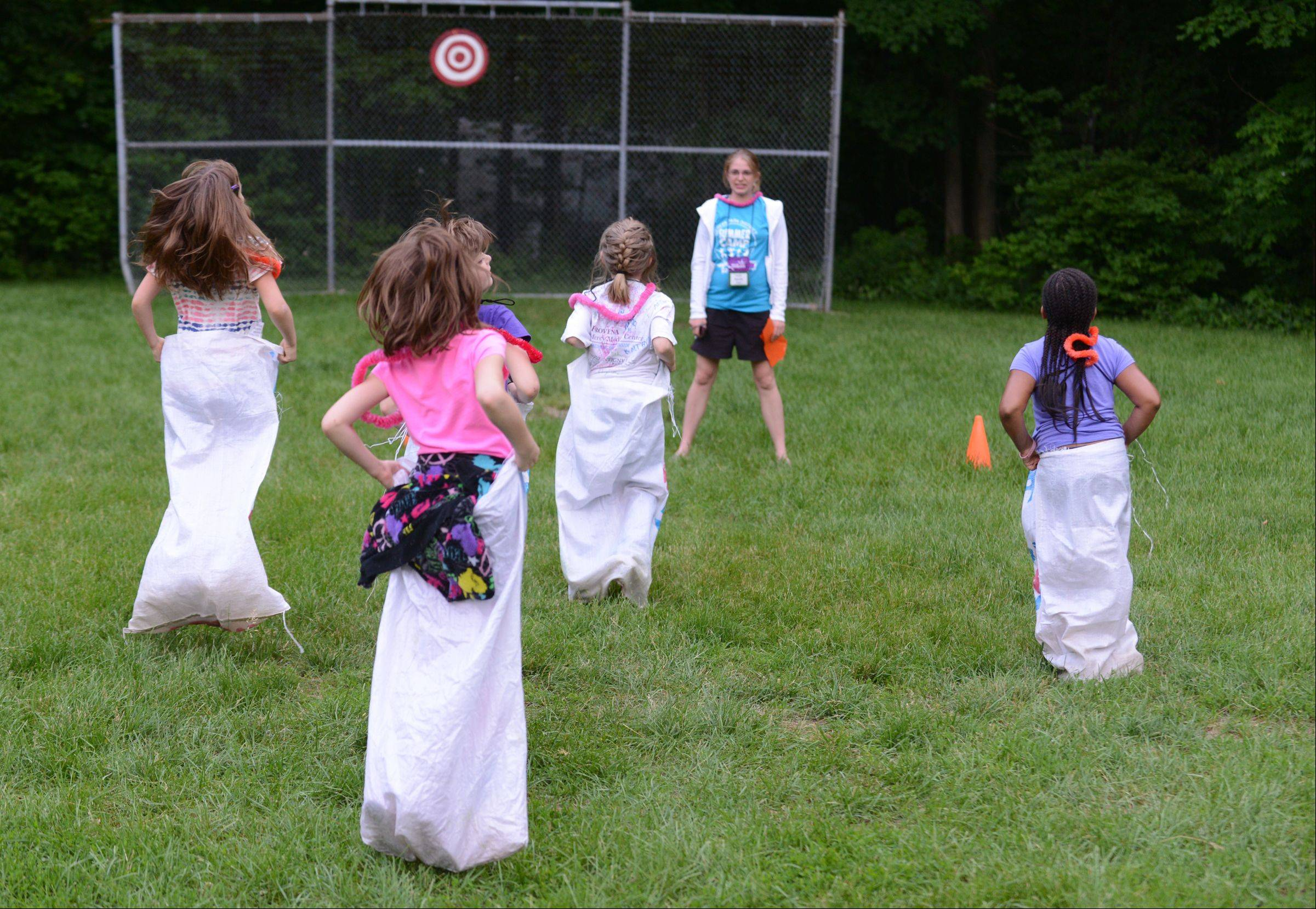 Royal Family Kids Camp counselor Sarah Walker of Geneva leads campers in a potato sack race as part of a camp luau.