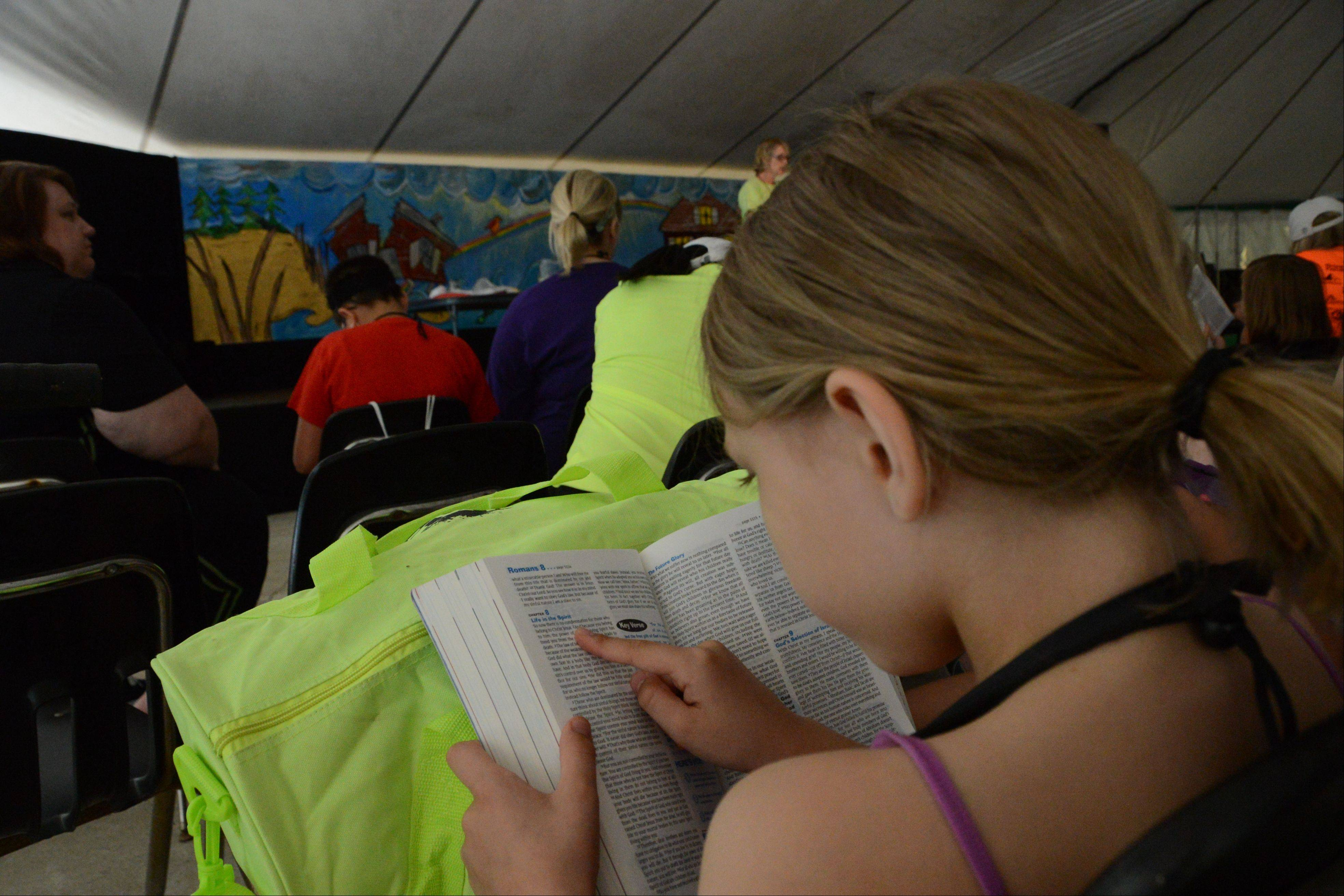 A camper uses her bible to follow along with the lesson at Royal Family Kids Camp in Wisconsin.