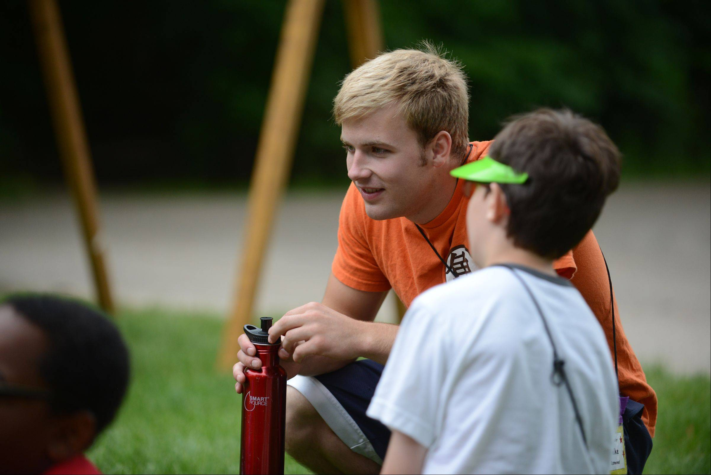 Royal Family Kids Camp counselor Mike du Vair listens to a story being told to him by his camper.