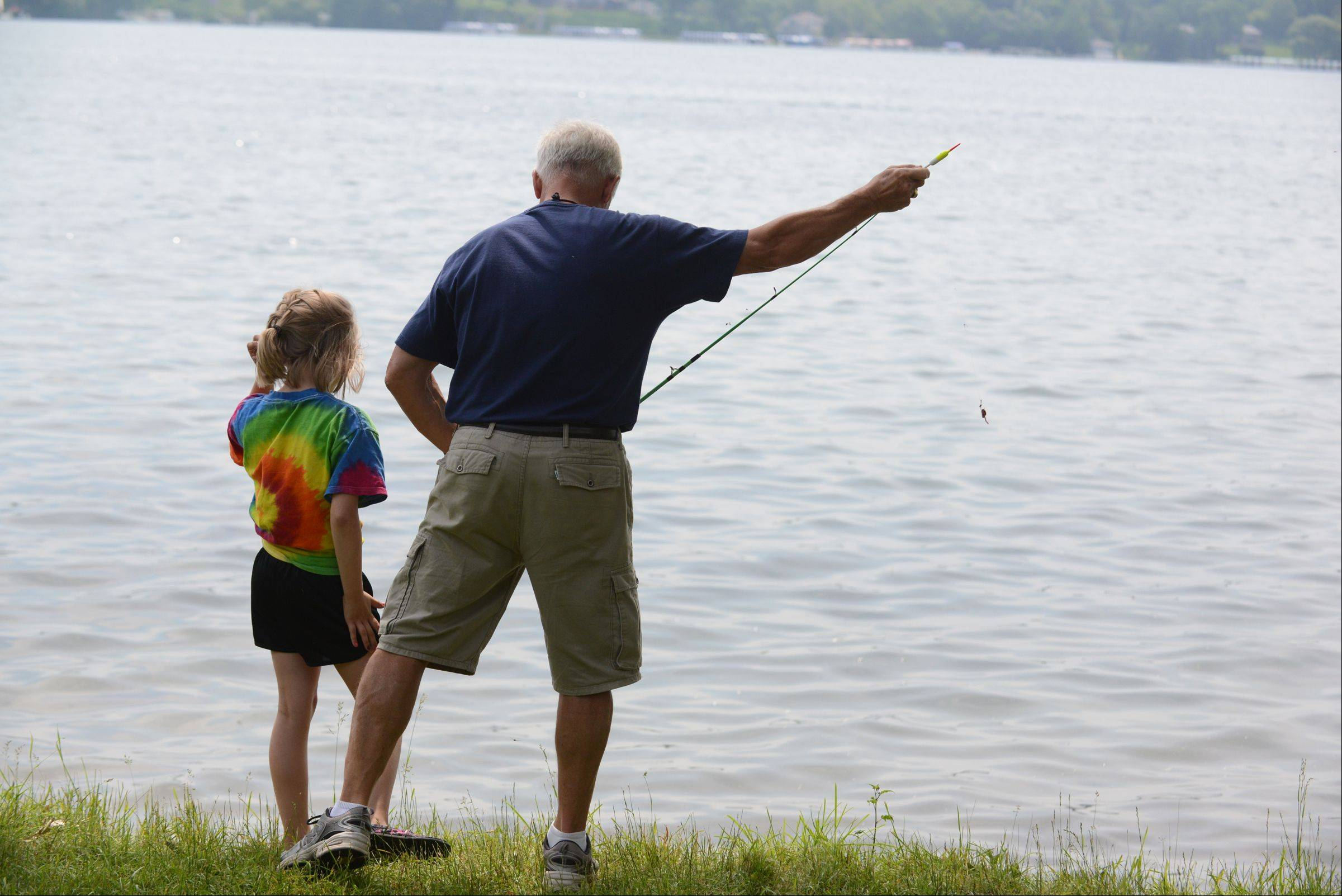 Royal Family Kids Camp counselor Jim Bates helps a camper fish at the Wisconsin camp. Fishing is one of the most popular things the campers do during their week at camp.