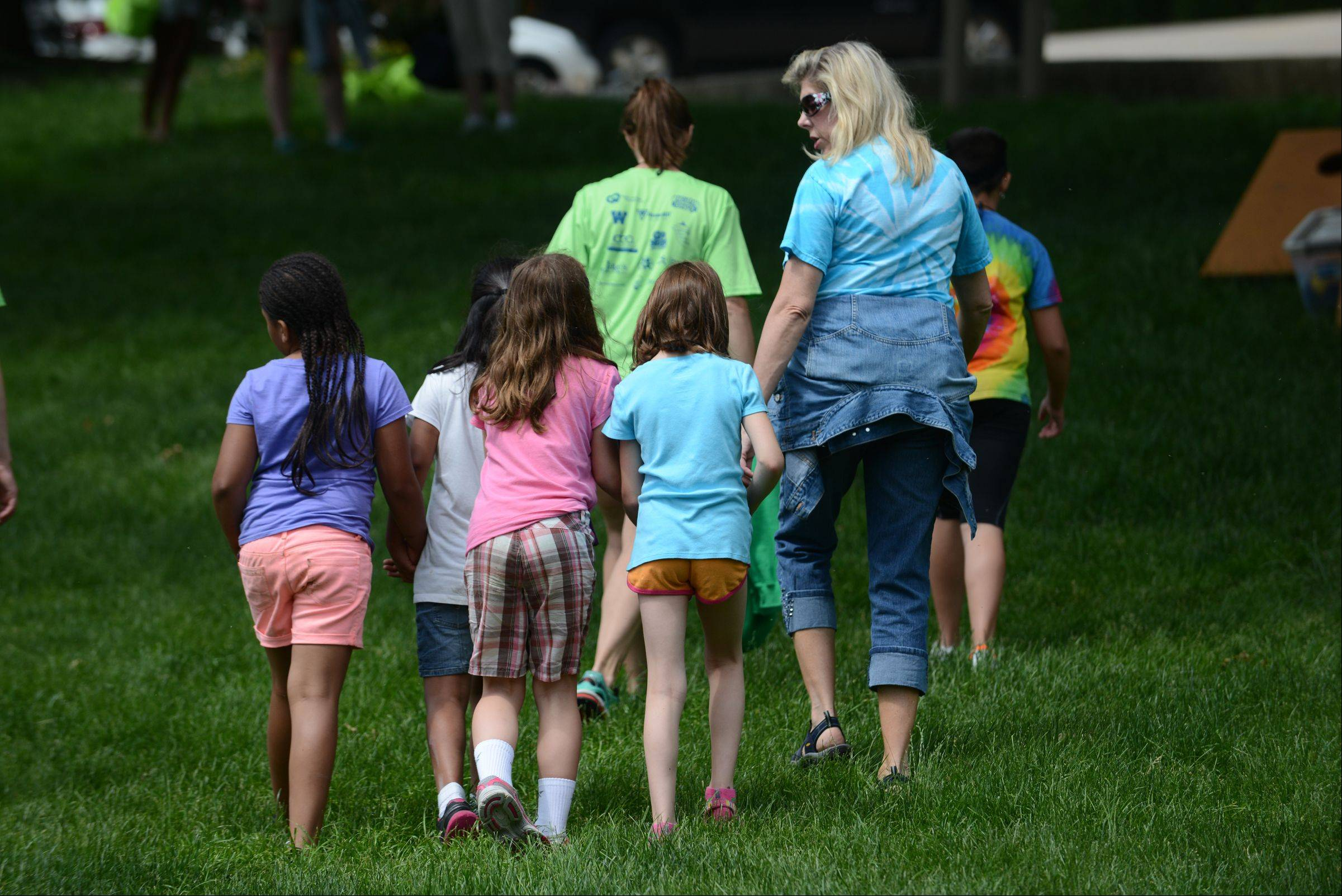 Royal Family Kids Camp counselor Karen Farley of Geneva leads a group of girls to one of the afternoon activities at the camp in Wisconsin.