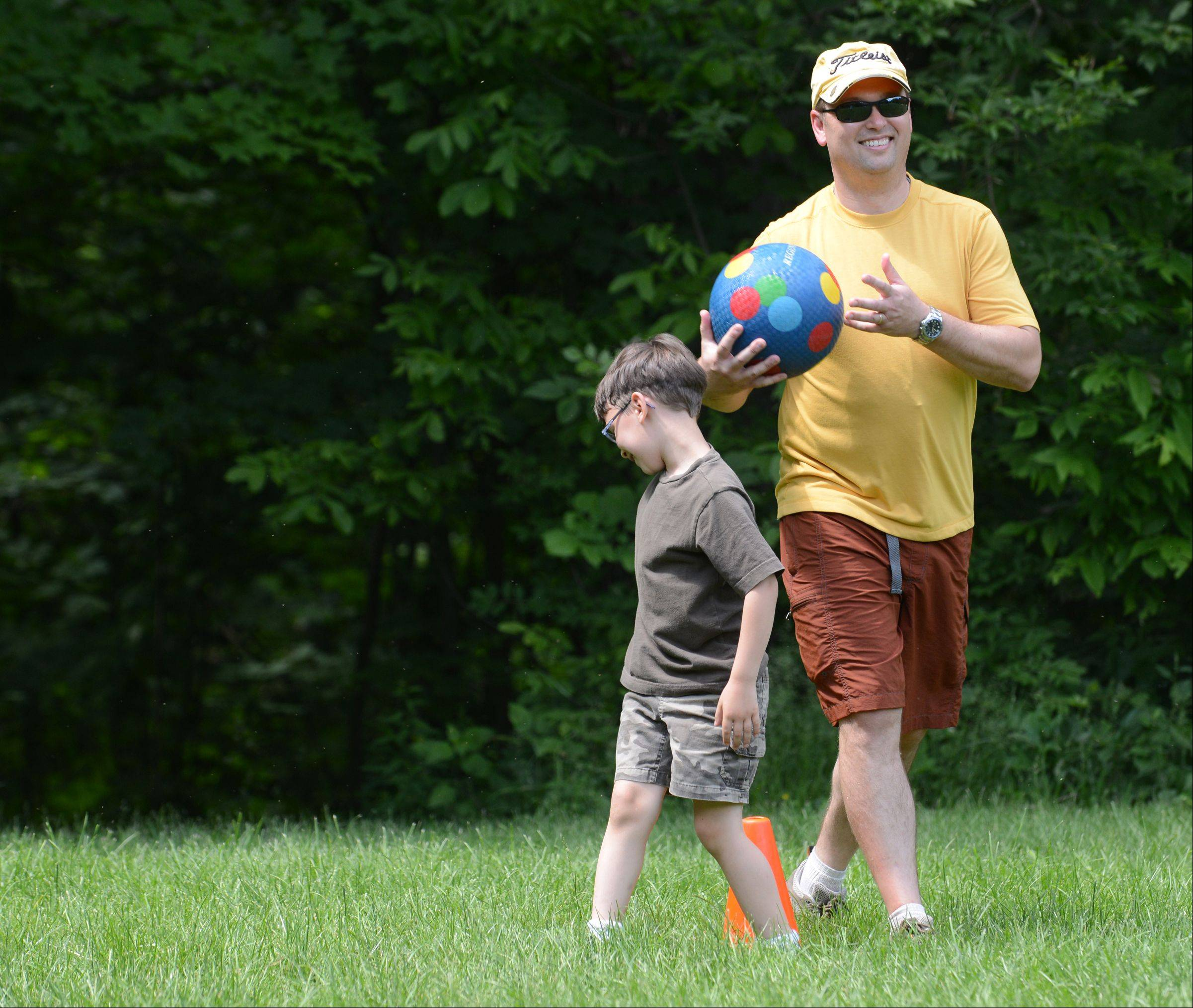 Royal Family Kids Camp counselor Mike Douglass of Geneva on the kick ball field with a camper.