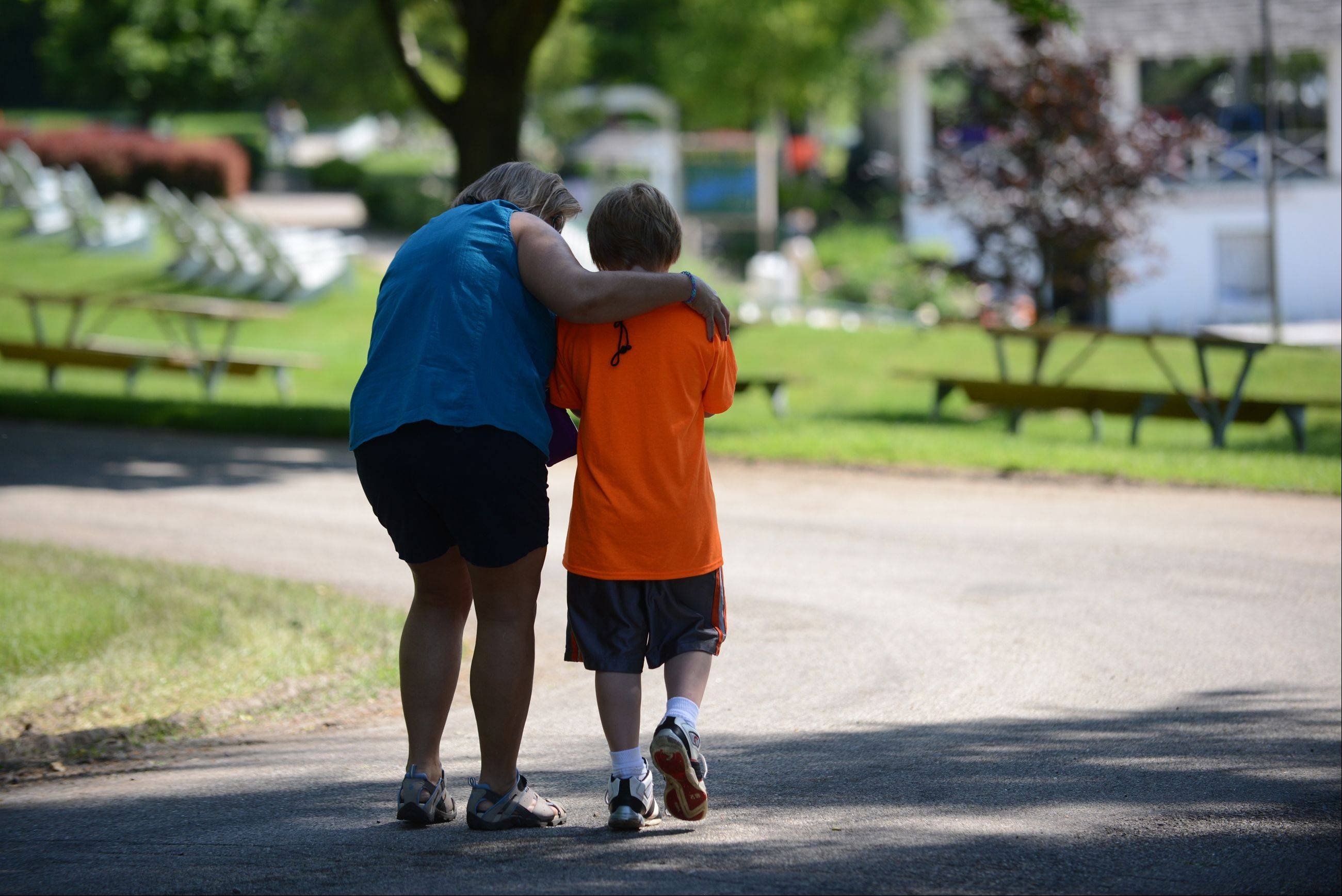 Royal Family Kids Camp Counselor Amy Wildman of Geneva comforts a camper as she walks with him at the camp in Wisconsin.